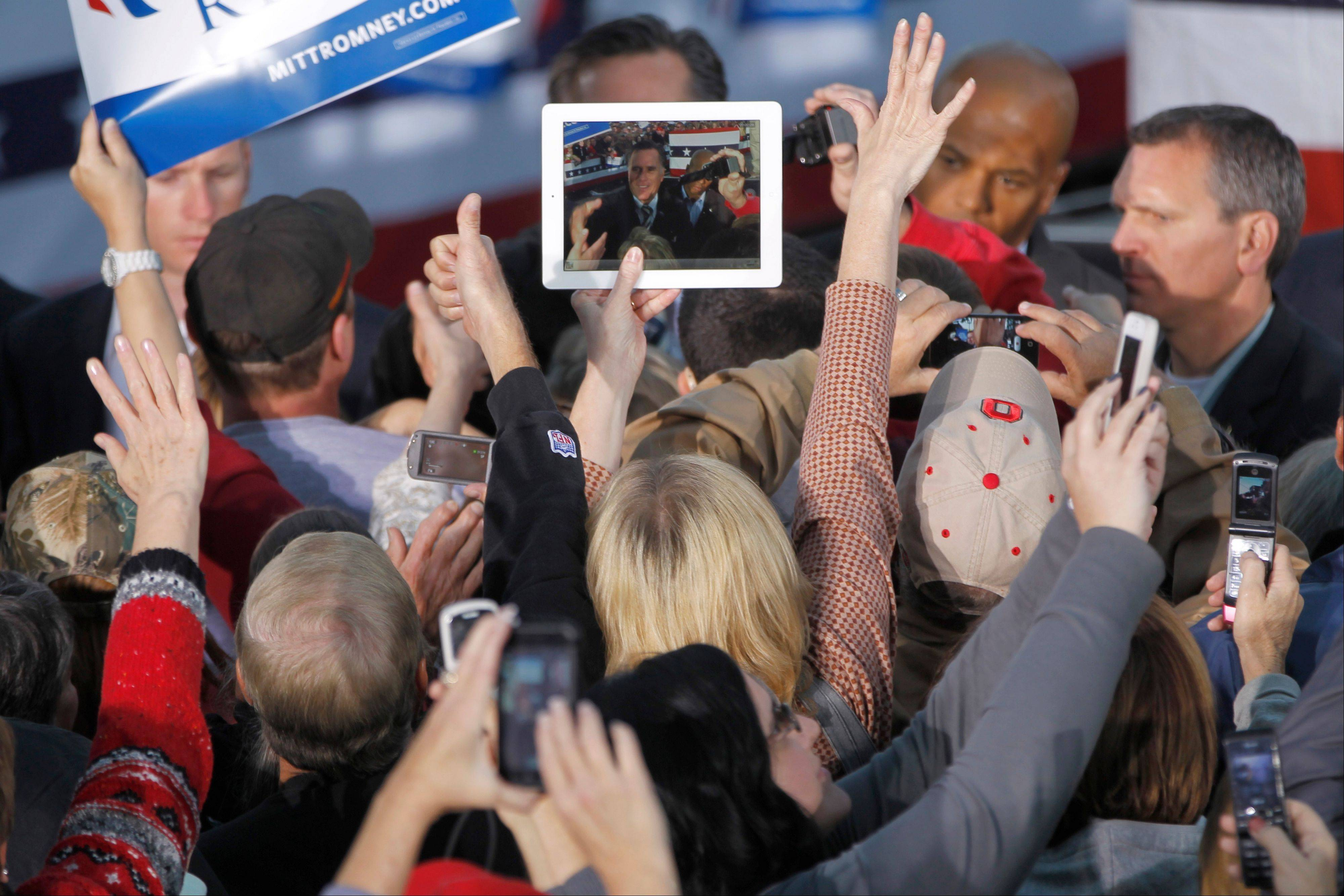 A supporter takes a picture with an iPad Friday of Republican presidential candidate and former Massachusetts Gov. Mitt Romney as he greets supporters at a campaign event in Lancaster, Ohio.