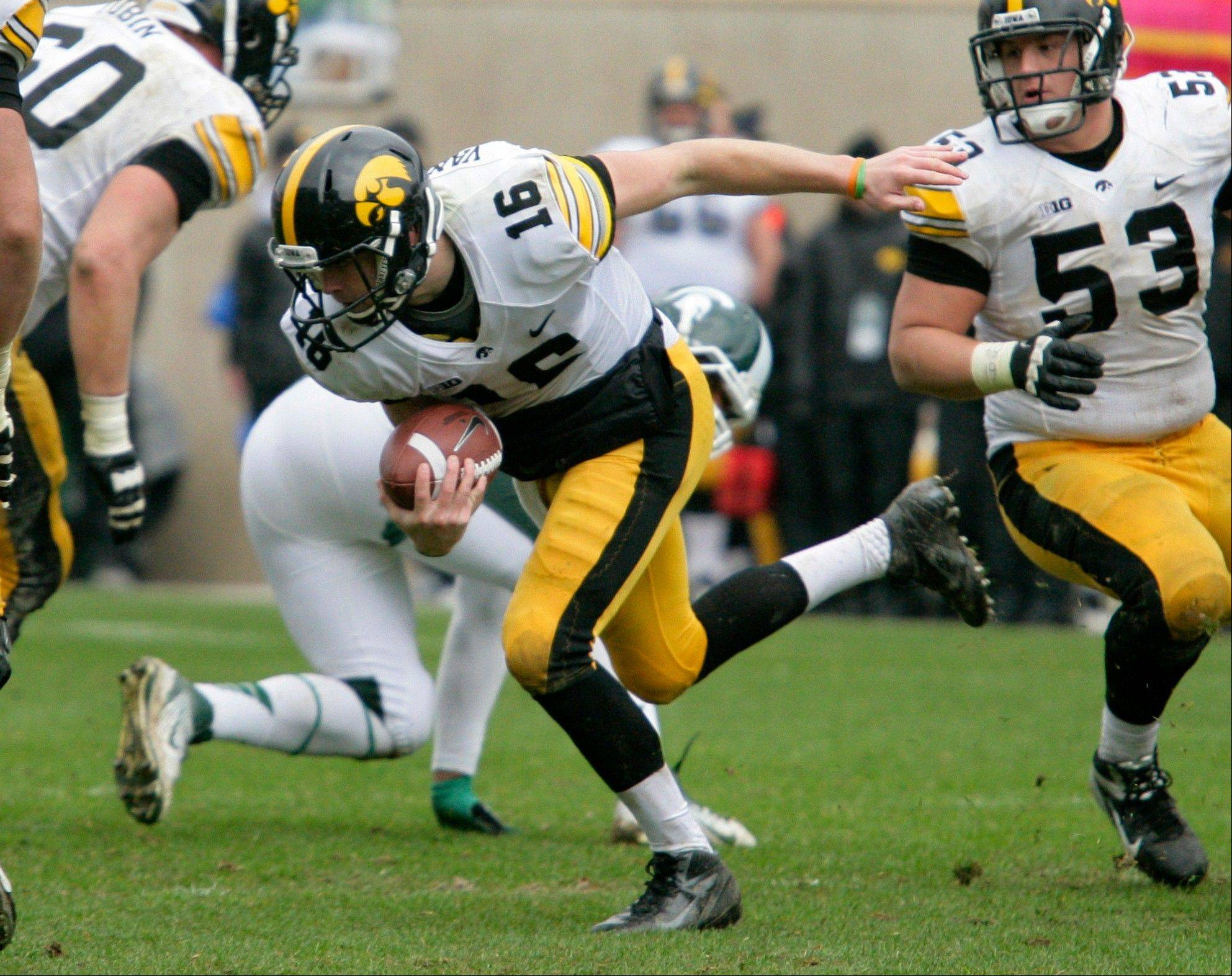 Iowa quarterback James Vandenberg scrambles between Matt Tobin, left, and James Ferentz (53) Saturday during the third quarter against Michigan State in East Lansing, Mich. Iowa won 19-16 in double overtime.