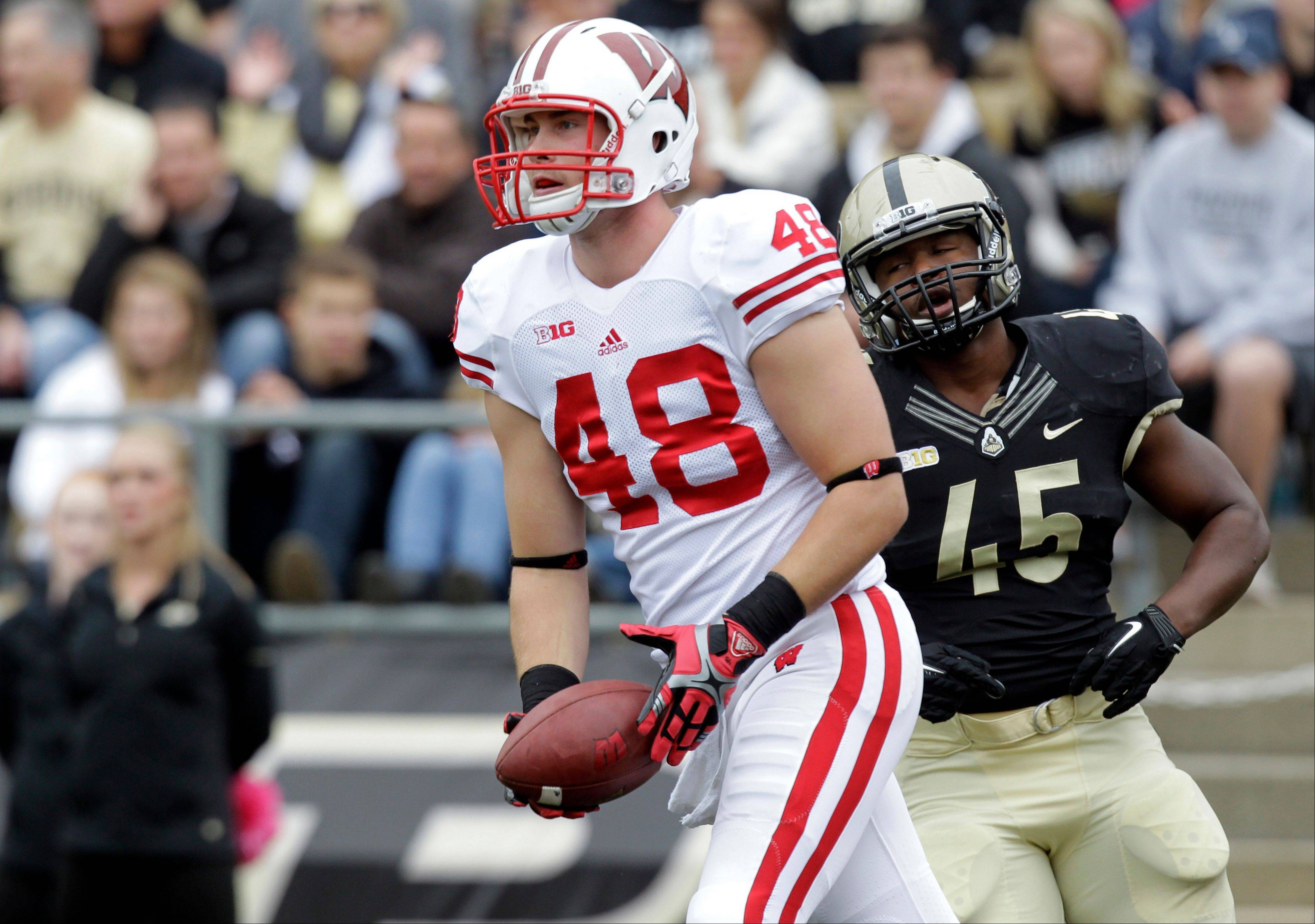Wisconsin tight end Jacob Pedersen tosses the ball back to the officials Saturday after scoring a touchdown in front of Purdue linebacker Will Lucas during the first half in West Lafayette, Ind.