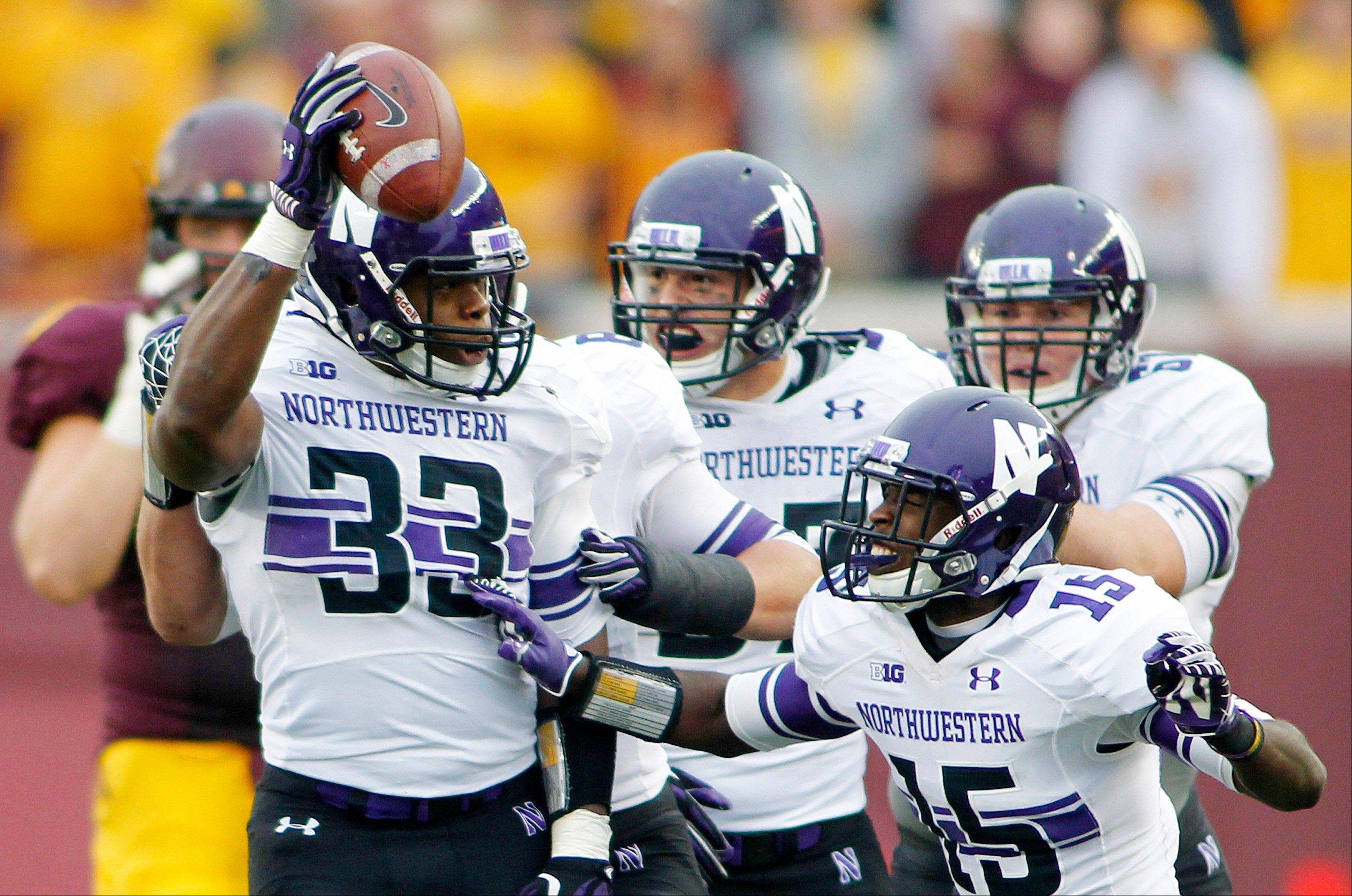 Northwestern linebacker David Nwabuisi celebrates Saturday with teammate Daniel Jones after intercepting a pass in the first half against Minnesota in Minneapolis.