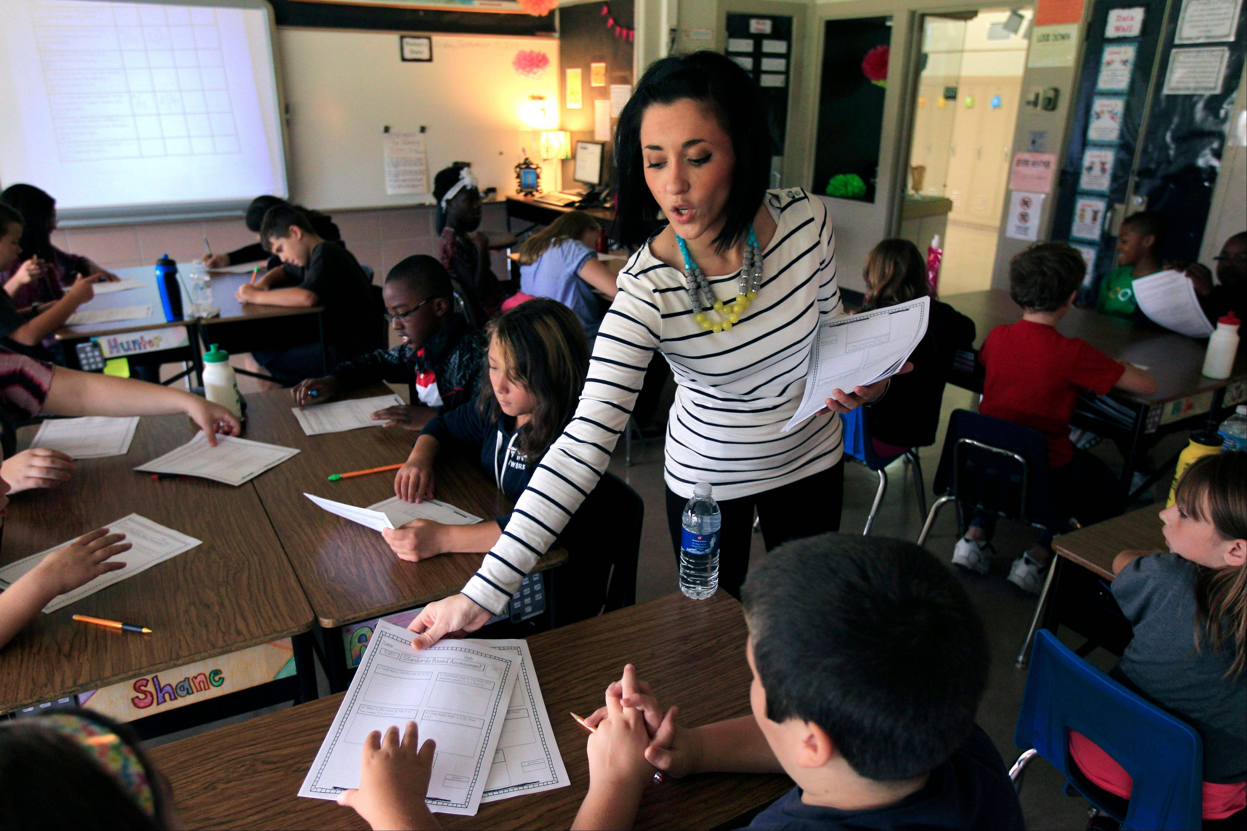 Kristine Nannini passes out student data sheets she created to her fifth grade class at McGrath Elementary in Grand Blanc, Mich.