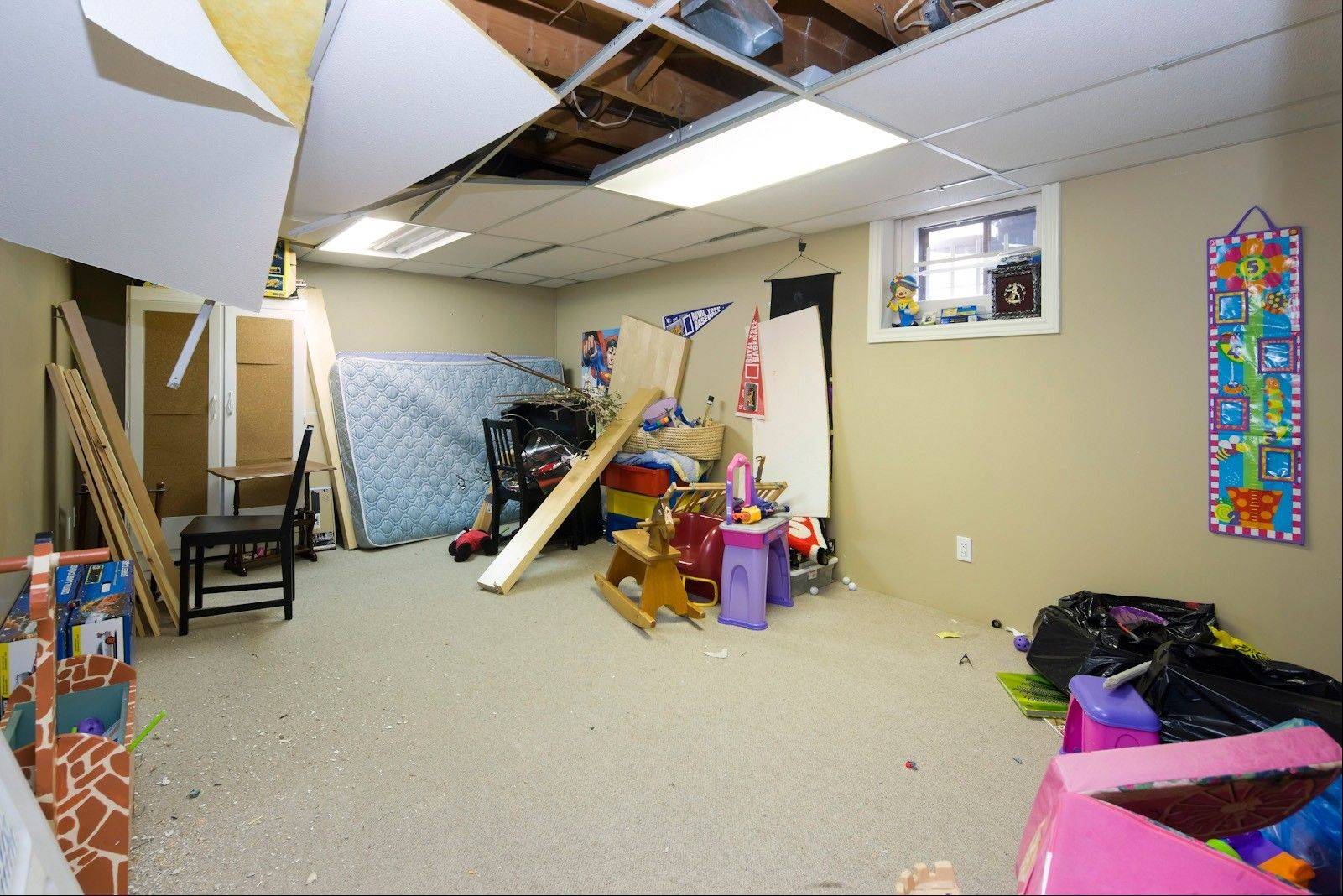 The lower level of this bungalow had a lot of space, but was a total disaster. It had become the final resting place for discarded toys and old furniture, and even the drop ceiling was tired and falling down.