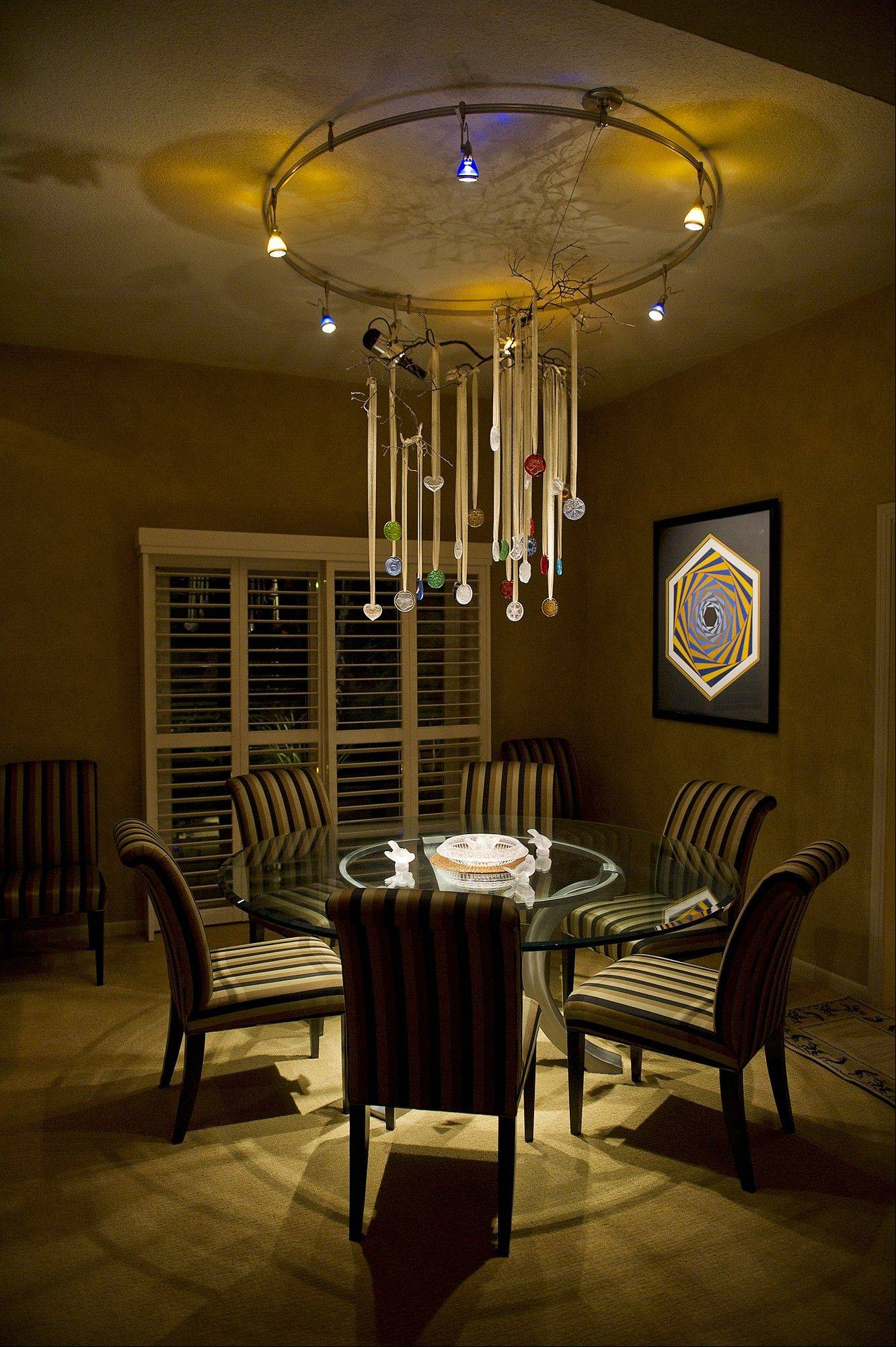Crystal ornaments catch the illumination from LED and halogen lights in this chandelier designed by Michael Sestak.