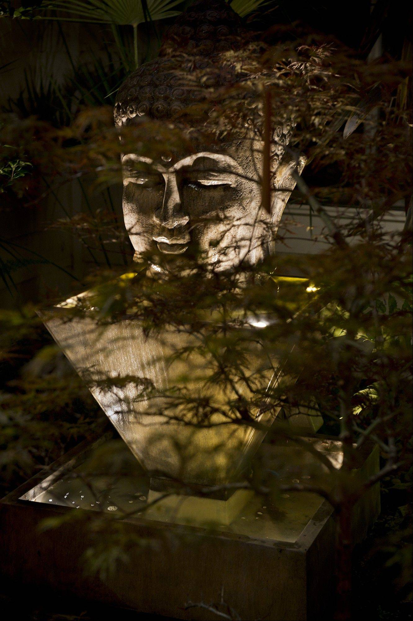 A Buddha fountain bathes in an LED glow in the entryway of Michael Sestak's home.
