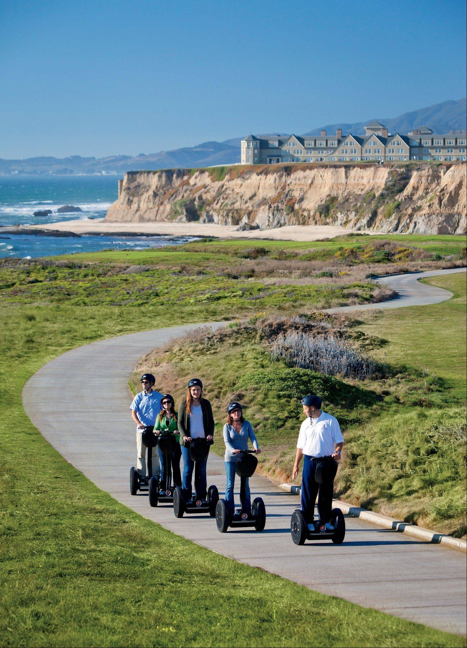 A hotel staff member leads a group of guests on a Segway tour of the Coastal Trail in Half-Moon Bay, Calif.