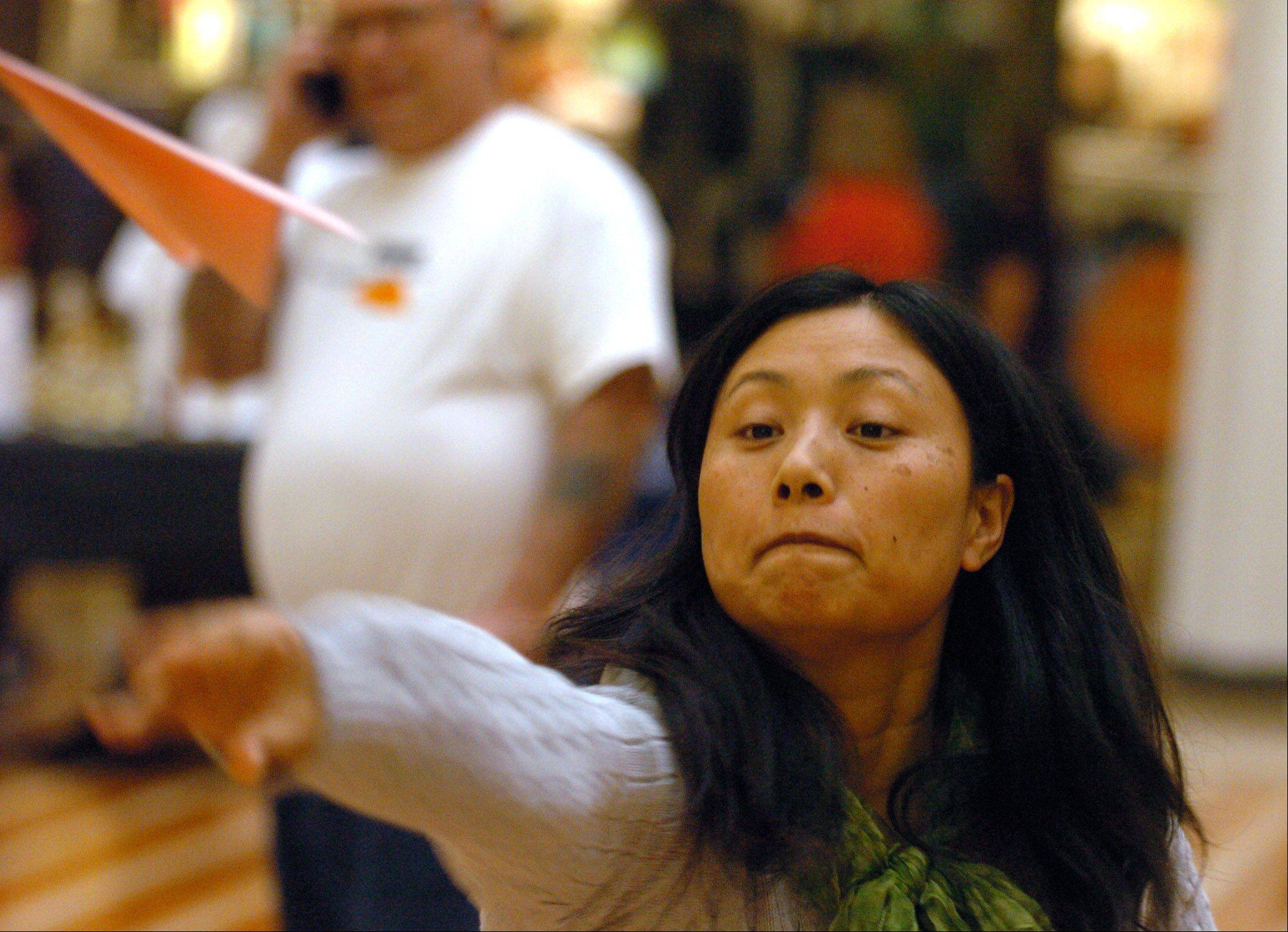 Charlene Gan of Naperville tosses a paper plane Saturday during Family Counseling Service's Aurora Paper Plane Air Show at Westfield Fox Valley mall.