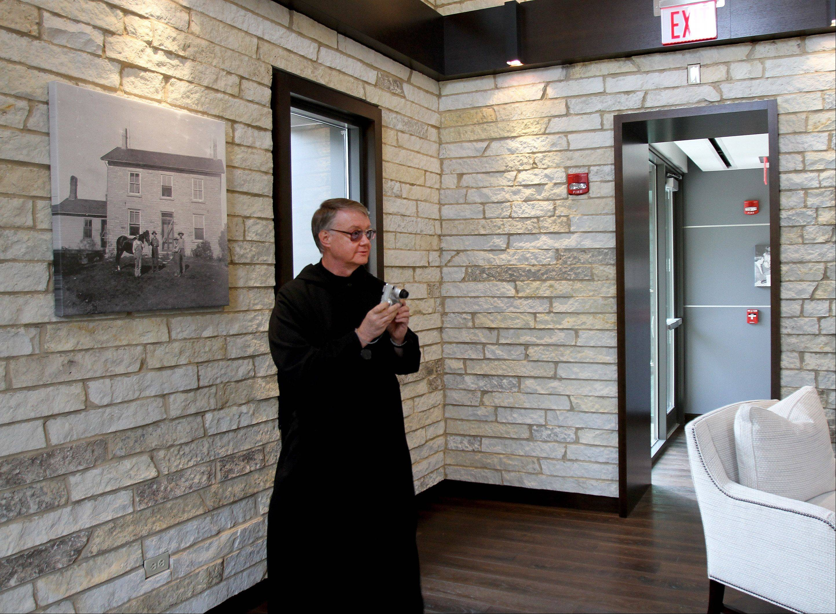 Brother Guy Jelinek, O.S.B., prior at Benedictine Abbey, gets some photos during the unveiling of the Neff Welcome Center at Benedictine University in Lisle. On the left is a photograph of the Neff Farmhouse, from which the new center is anchored.