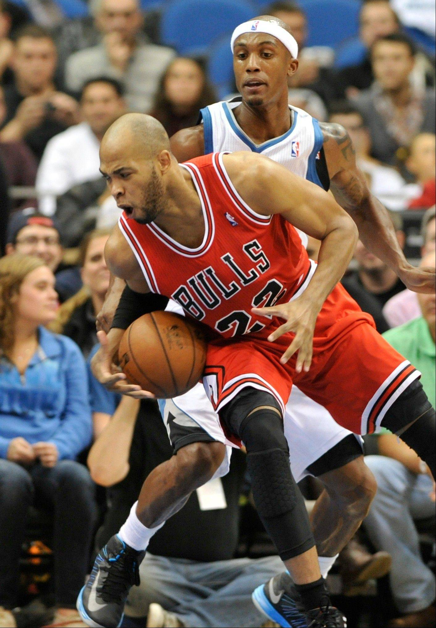 Chicago Bulls' Taj Gibson (22) tries to maintain balance as Minnesota Timberwolves' Dante Cunningham defends during the first half of an NBA preseason basketball game, Saturday, Oct. 13, 2012, in Minneapolis.