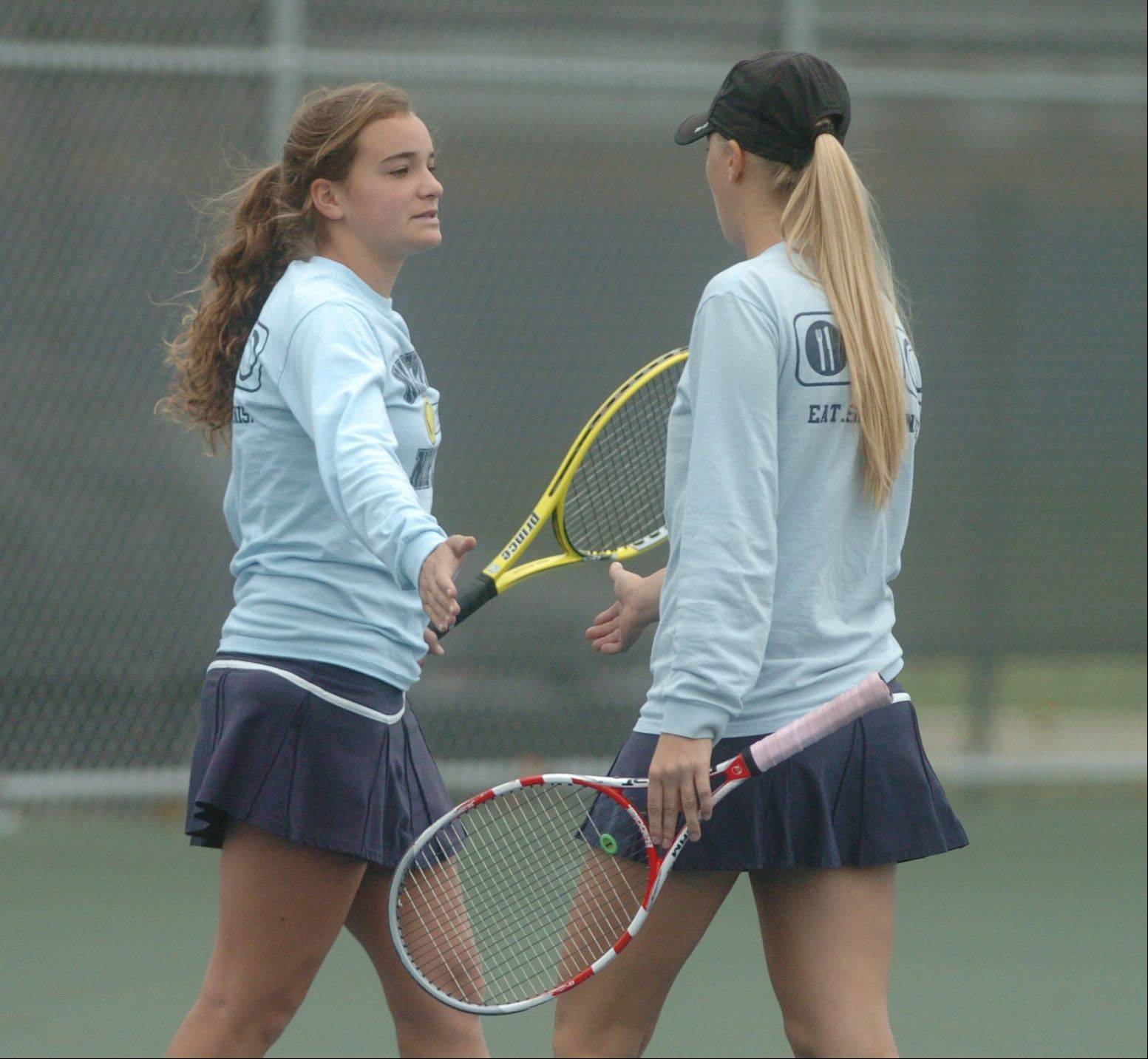 Tiffany Oken,left, and Kayla Maxson slap hands during a challengeing match against Naperville Central. This took place during the Naperville North girls tennis sectional at Naperville North High School Saturday.