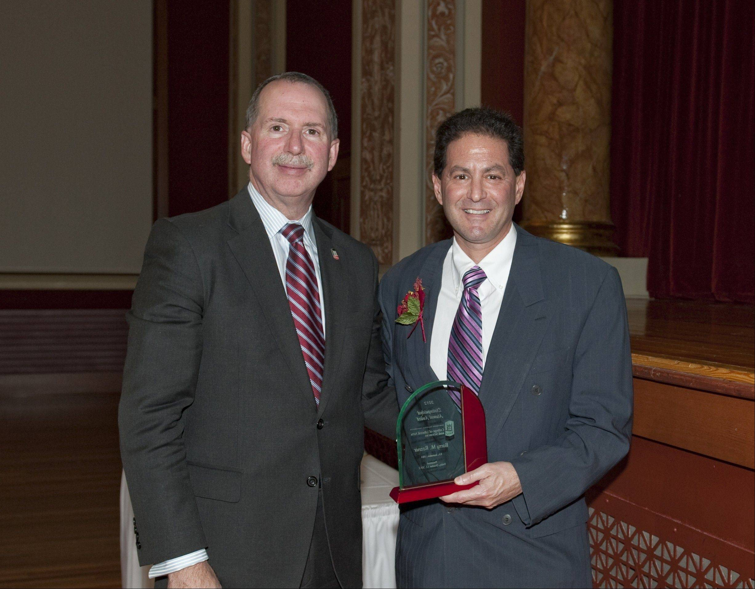 Daily Herald columnist Barry Rozner was presented Friday with a Distinguished Alumni Award by Christopher McCord, the dean of the College of Liberal Arts and Sciences at Northern Illinois University.