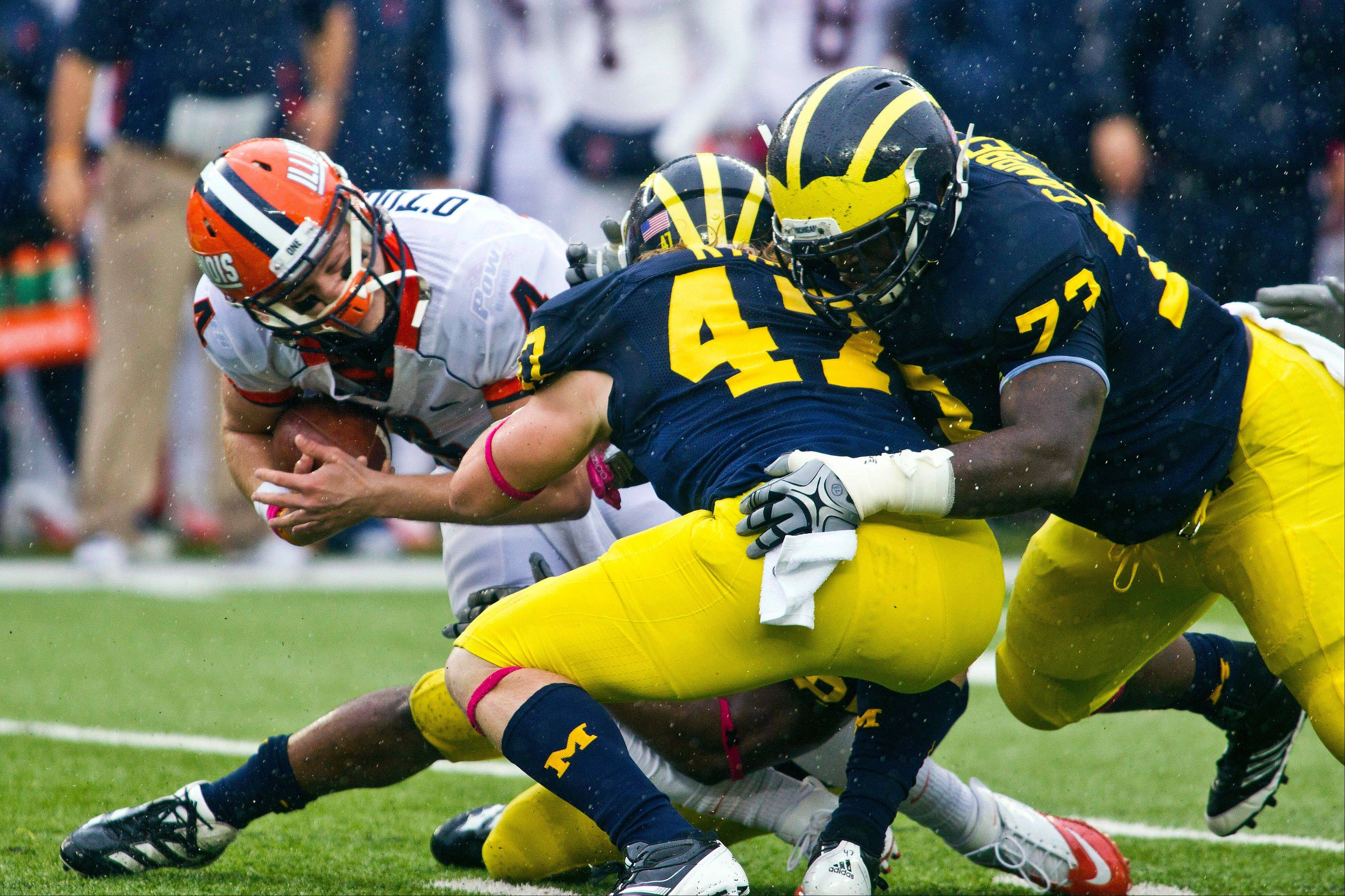 Illinois quarterback Reilly O'Toole is tackled by Michigan linebacker Jake Ryan (47) and defensive tackle William Campbell, right, Saturday during the second quarter in Ann Arbor, Mich.