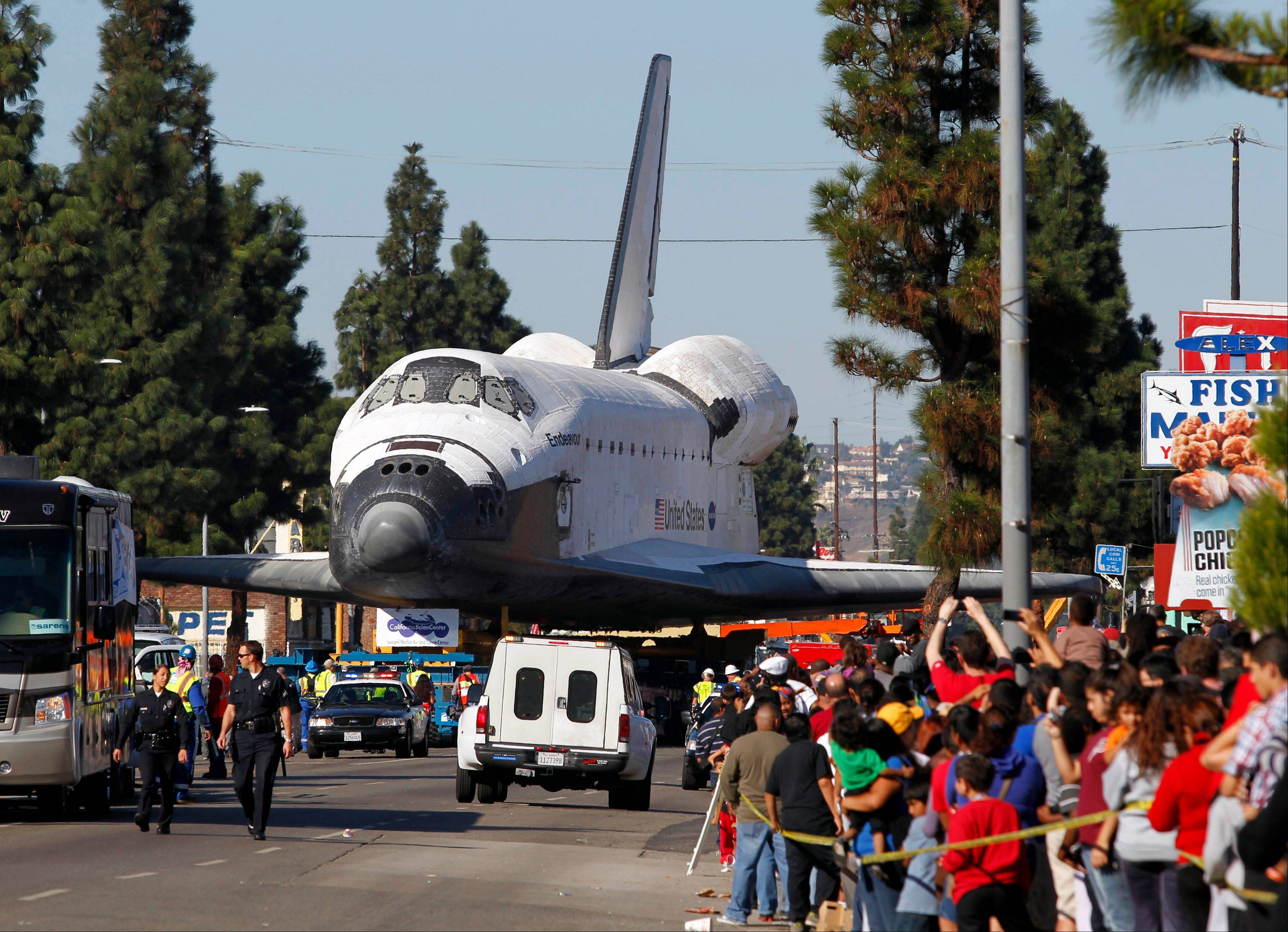 Fans watch Endeavour slowly move down Martin Luther King Blvd. in Los Angeles Sunday.