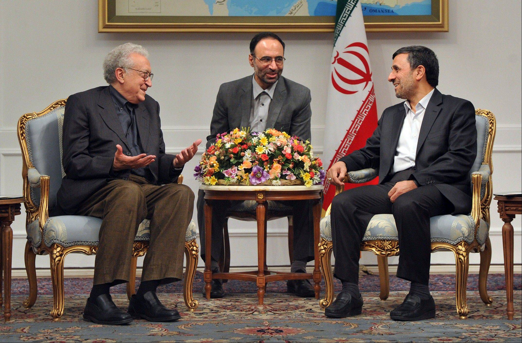 U.N. envoy on Syria, Lakhdar Brahimi, left, talks with Iranian President Mahmoud Ahmadinejad, during their meeting in Tehran, Iran, Sunday. An unidentified interpreter sits at center.