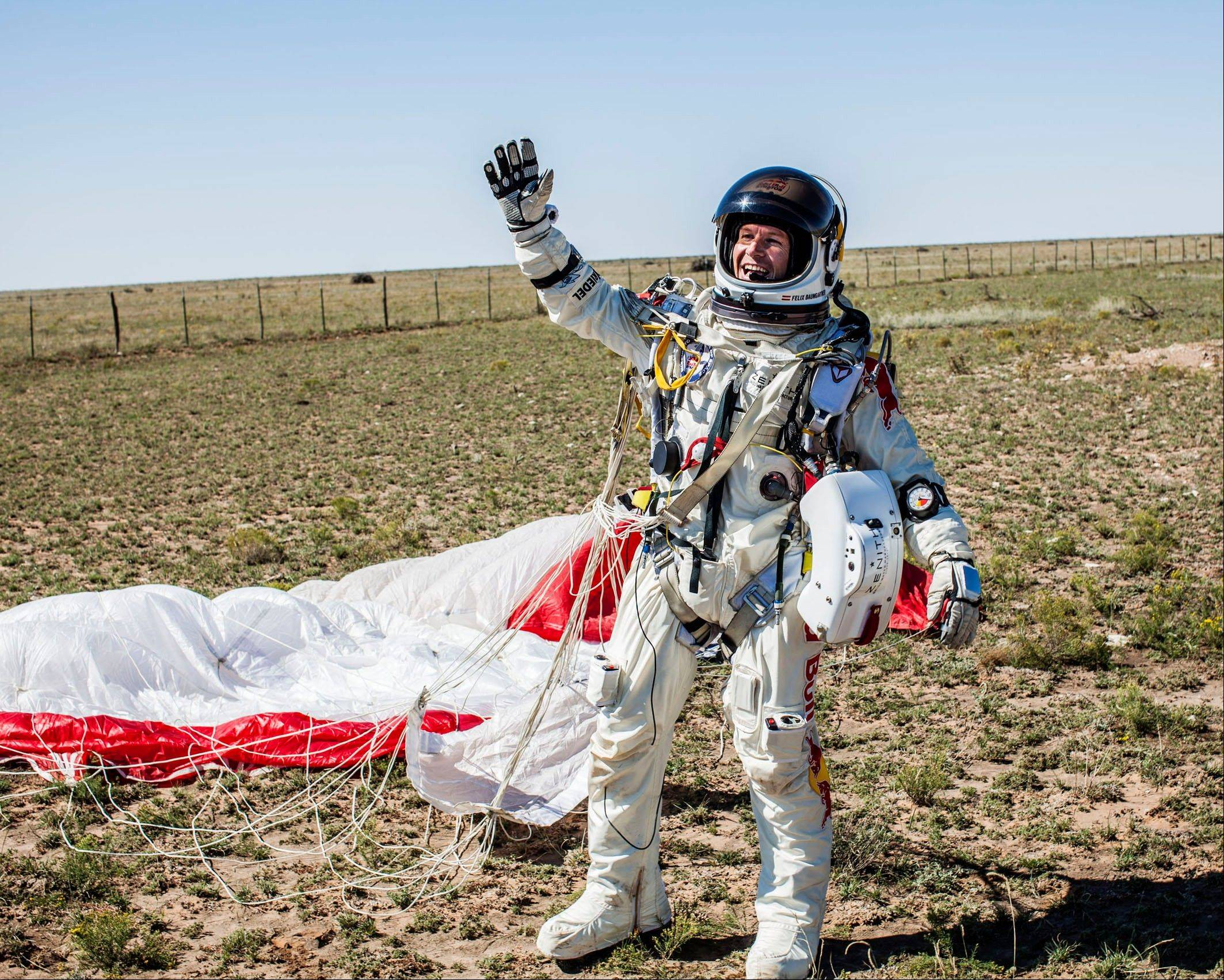 In this photo provided by Red Bull Stratos, Pilot Felix Baumgartner of Austria celebrates after successfully completing the final manned flight for Red Bull Stratos in Roswell, N.M., Sunday, Oct. 14, 2012.�Baumgartner came down safely in the eastern New Mexico desert minutes about nine minutes after jumping from his capsule 128,097 feet, or roughly 24 miles, above Earth.