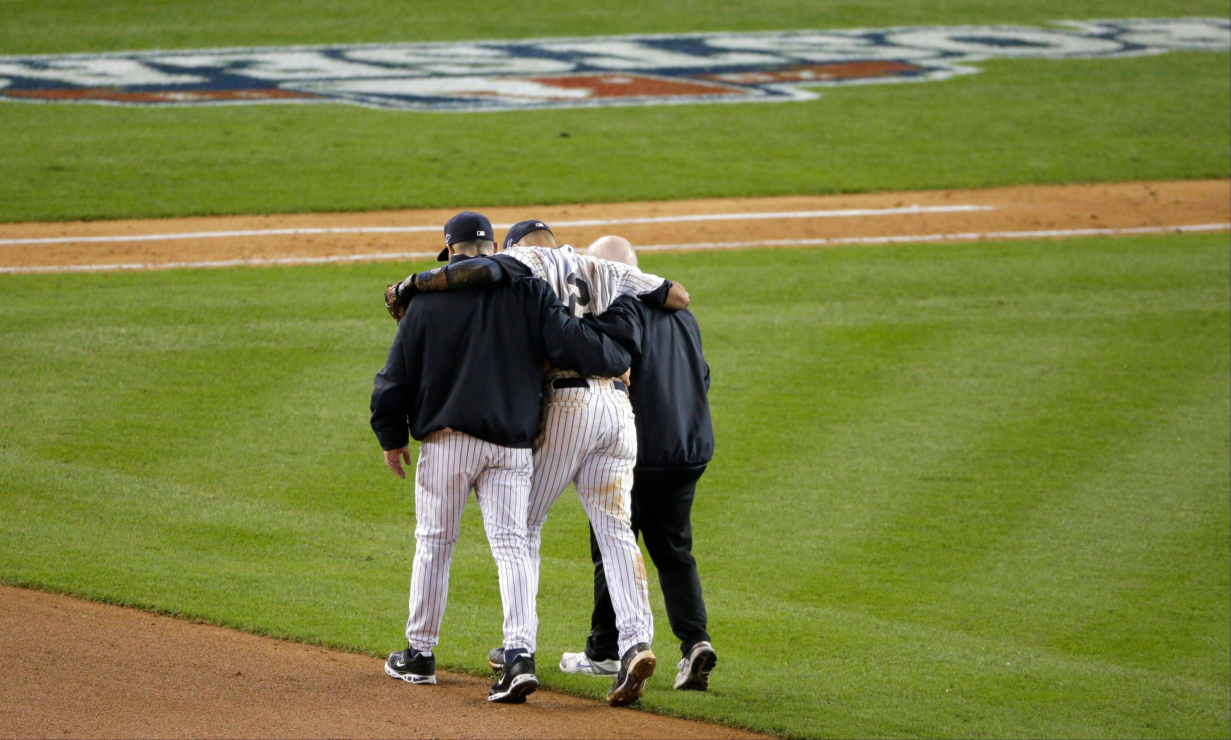 Trainer Steve Donohue, right, and New York Yankees manager Joe Girardi, left, help Yankees' Derek Jeter off the field after he injured himself during Game 1 of the American League championship series against the Detroit Tigers Sunday, Oct. 14, 2012, in New York.