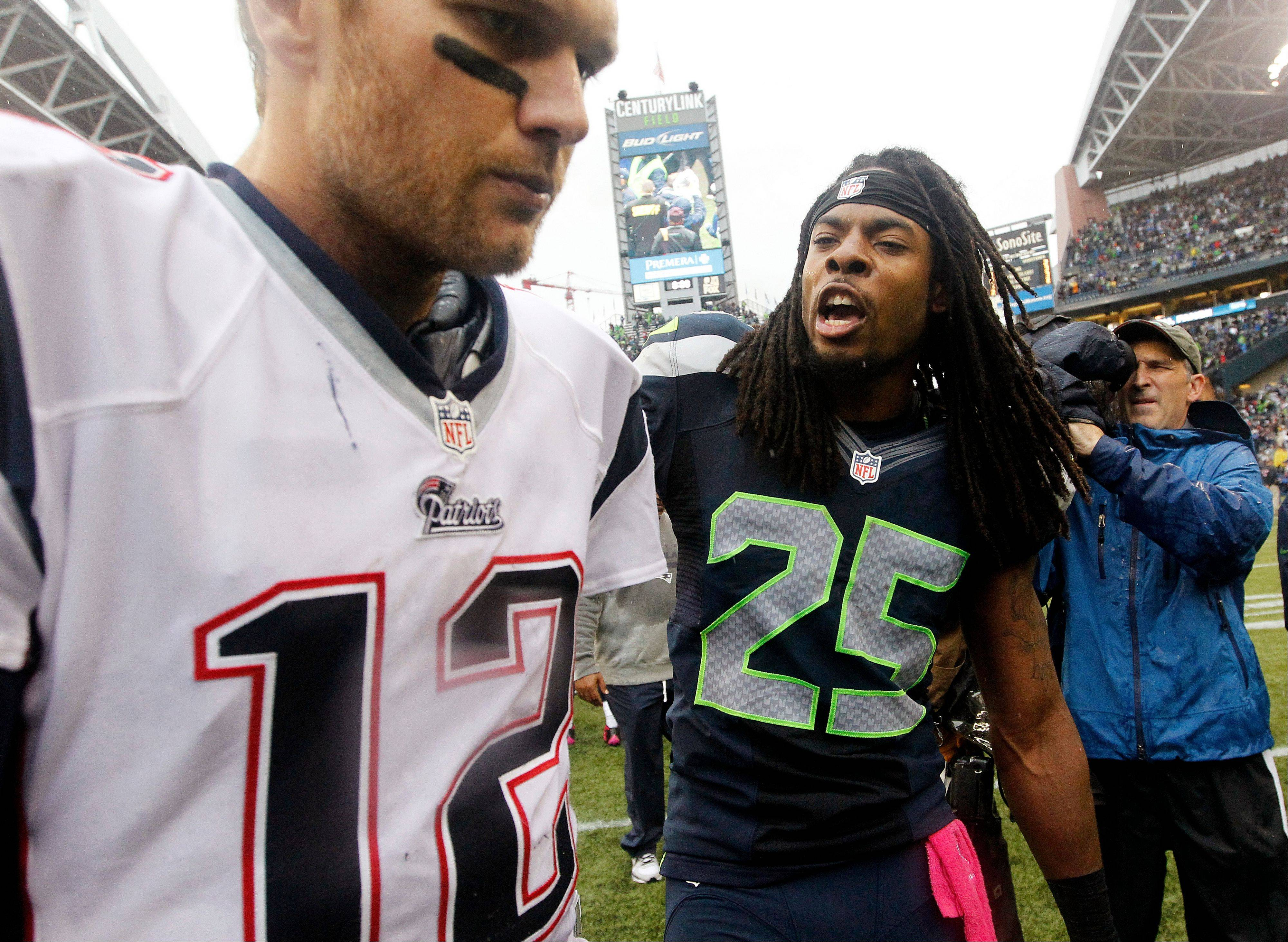 Seattle Seahawks' Richard Sherman (25) talks with New England Patriots quarterback Tom Brady on Sunday in Seattle. The Seahawks won 24-23.