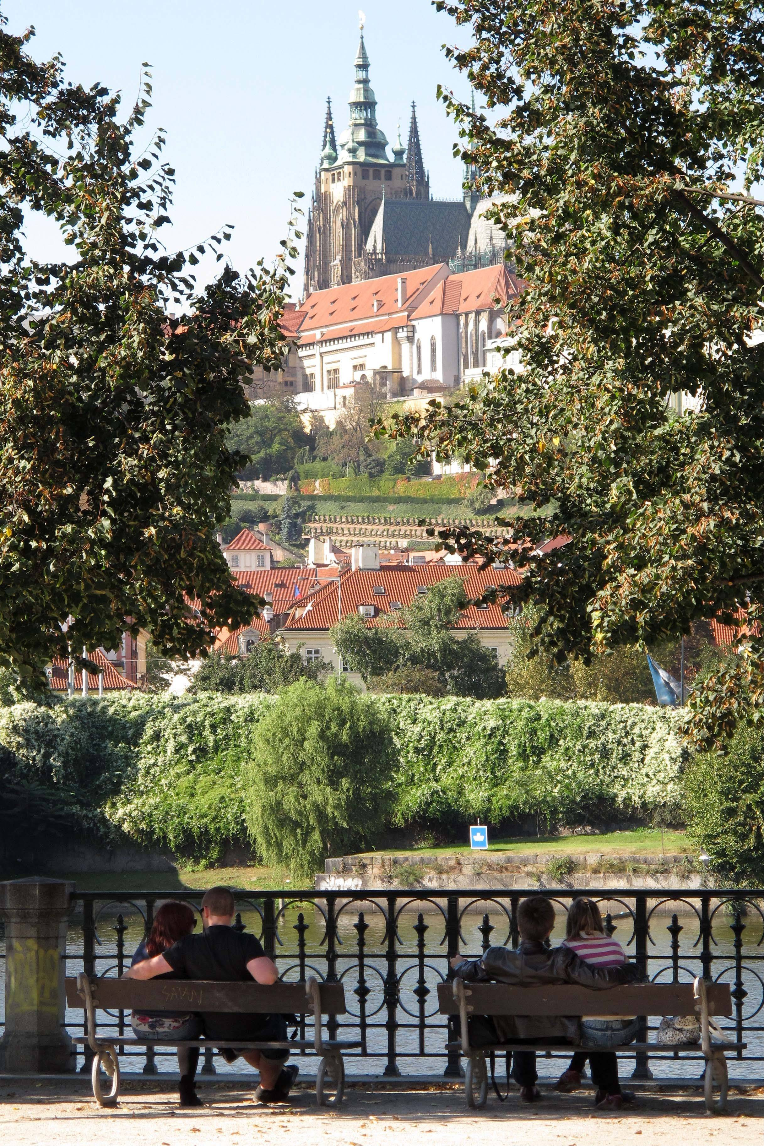 Two couples sit on the bank of the Vltava River with a medieval castle in the background in Prague.