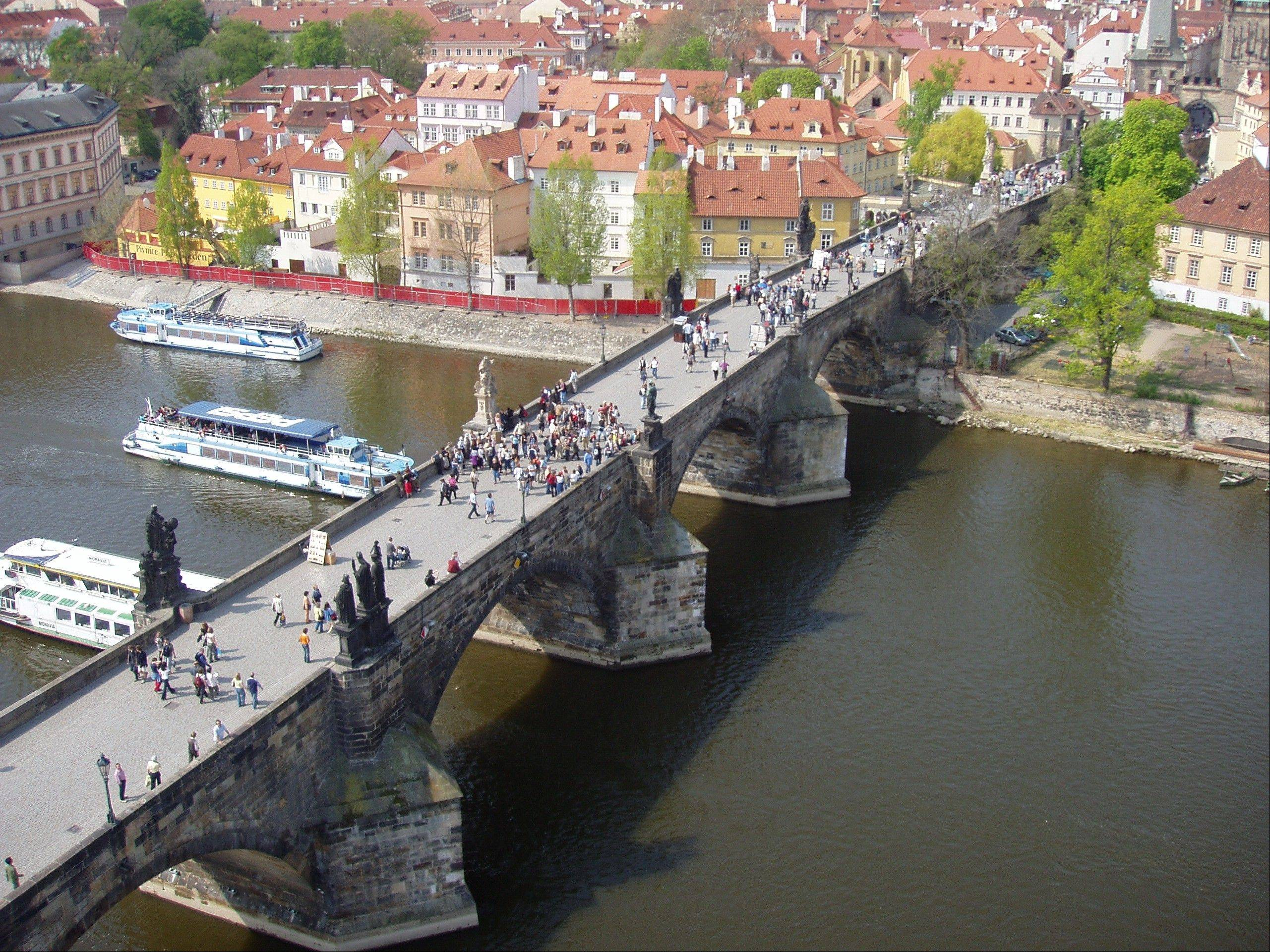 People walk over the Charles Bridge in Prague, Czech Republic. The bridge's construction began in 1357 under Charles IV, the Holy Roman Emperor known as the father of the Czech nation.