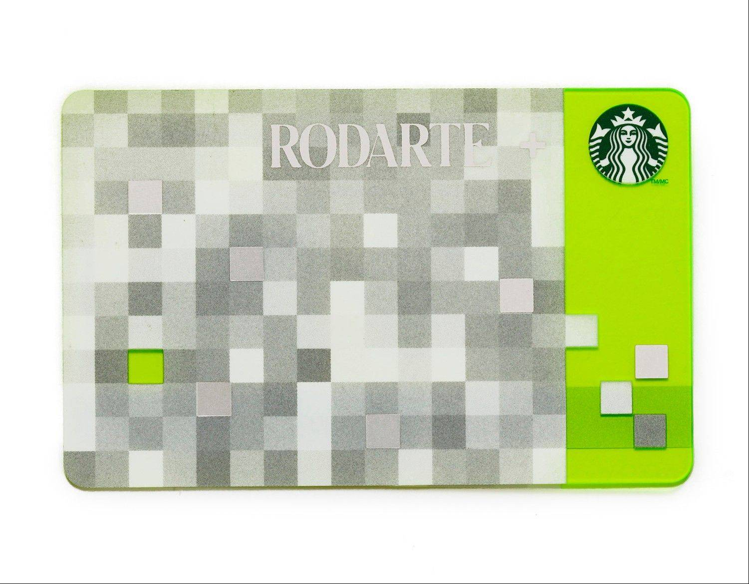 This product image released by Starbucks shows the Rodarte design Starbucks gift card, part of a series of limited-edition products for the holiday season. The card is one of several Rodarte-designed items including tote bags, cup sleeves and mug. The signature pattern features a pixelated checkerboard of gray, white and silver set against different shades of green.
