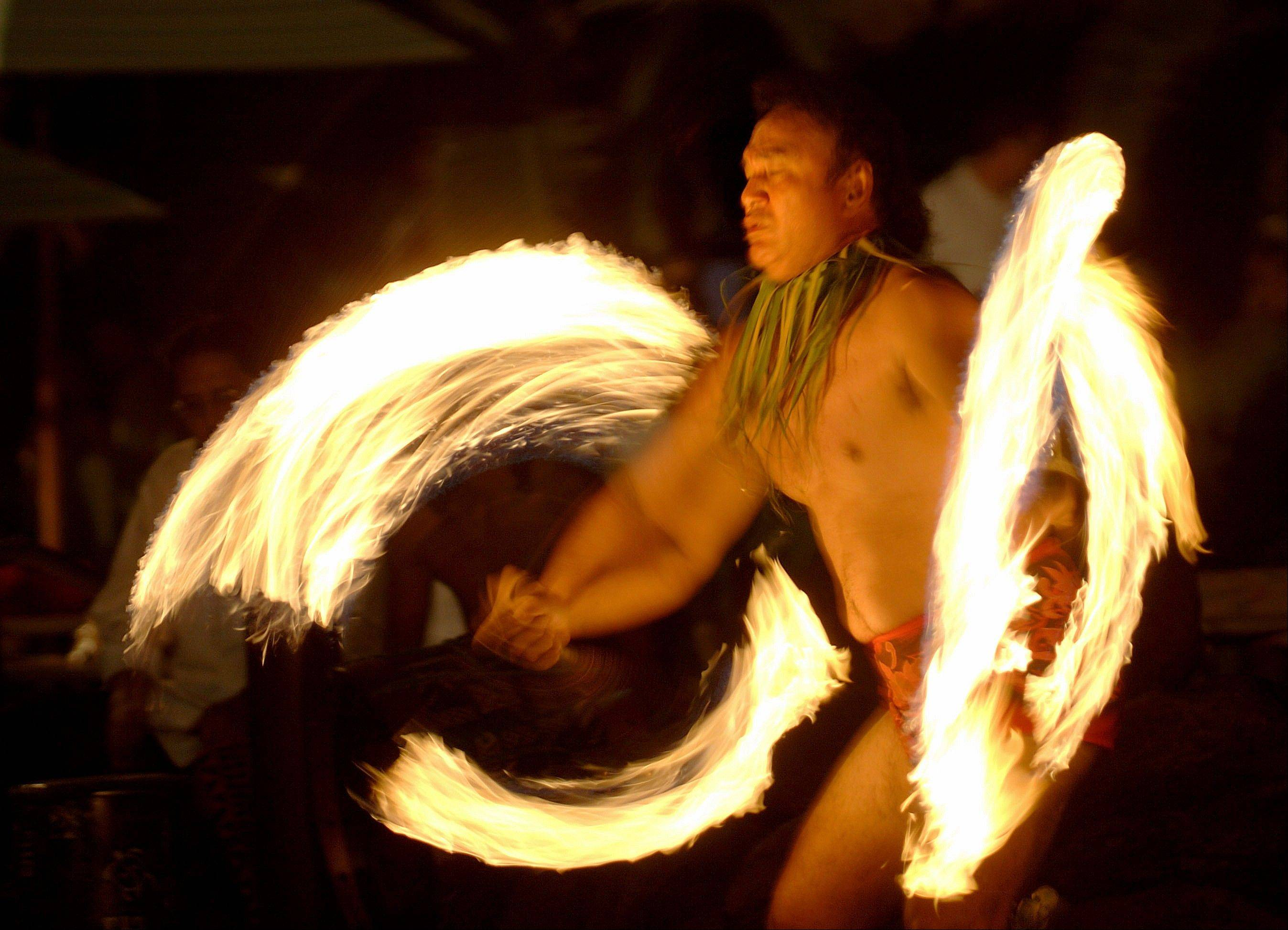 "Vise Vitale of Honolulu performs a Samoan fire knife dance during in an ""Aloha Friday"" celebration of Polynesian music song and dance in Honolulu. Fire knife dancing is often mistaken for Hawaiian even though it's a Samoan invention."
