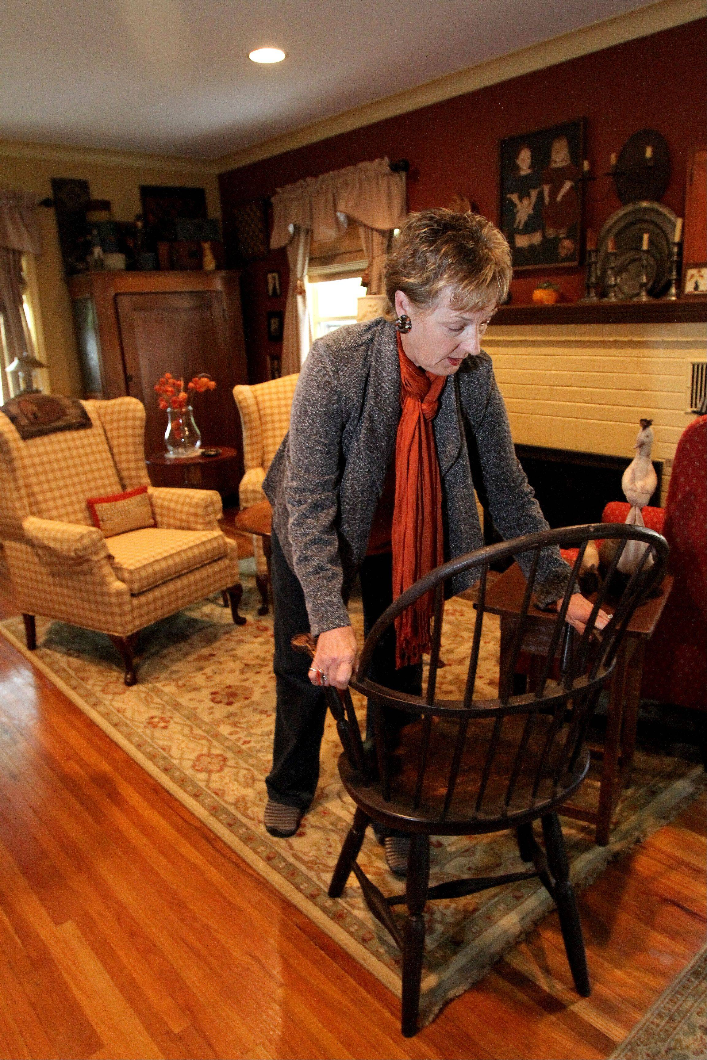 Linda Buehrer of Downers Grove shows her favorite chair, a Windsor from the 1780s. She bought the chair at a previous Fox Valley Antiques Show.
