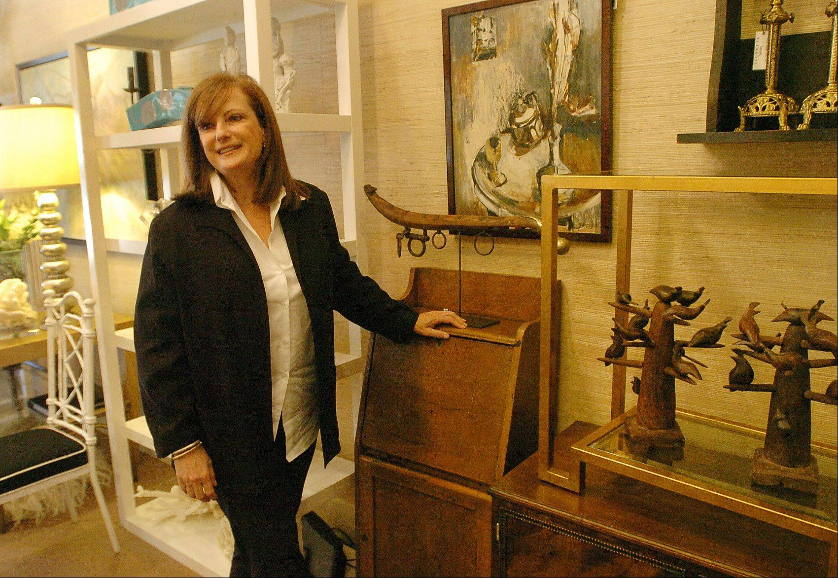Designer Missie Bender in her shop in Glencoe called Vignette Home, with an early American telephone cabinet picked from Indiana, and hand-carved American folk art birds from Michigan.