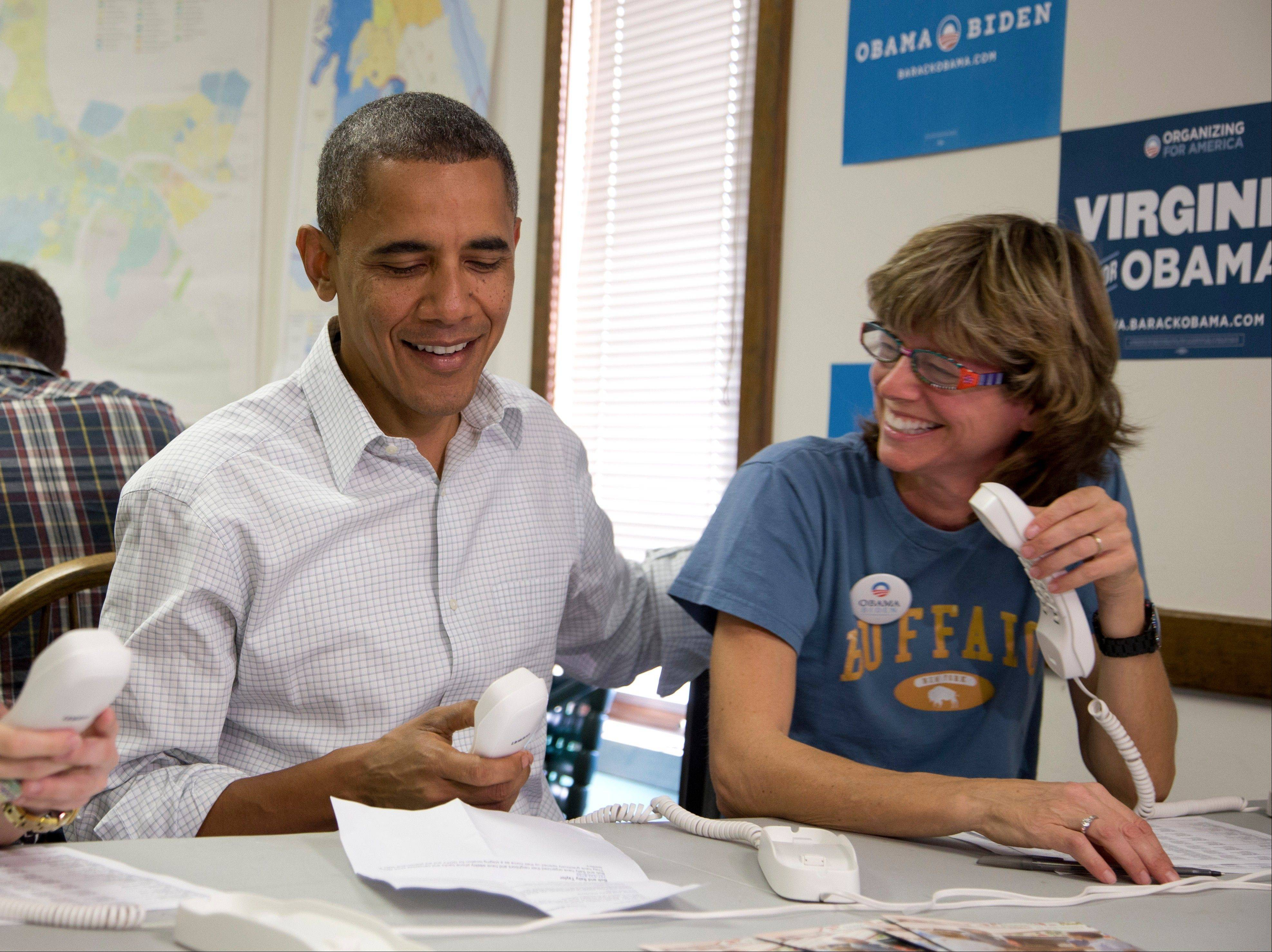 President Barack Obama makes phone calls to volunteers at an Organizing for America field office with Suzanne Stern, right, Sunday in Williamsburg, Va.