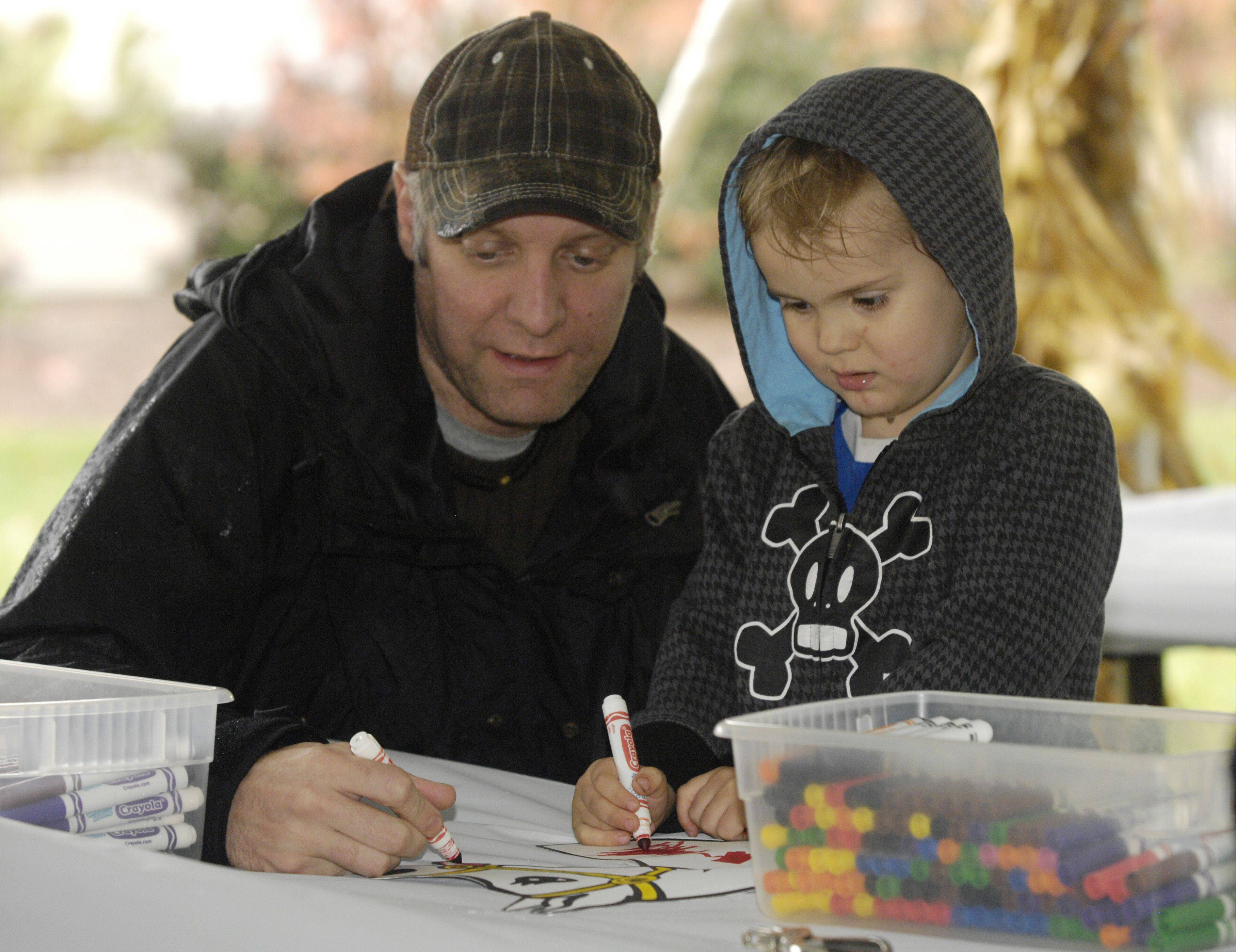 Eric Fey and his son Nolan, 3, make a hobby horse while visiting the Forest Preserve District of DuPage County's annual Danada Fall Festival Sunday in Wheaton.