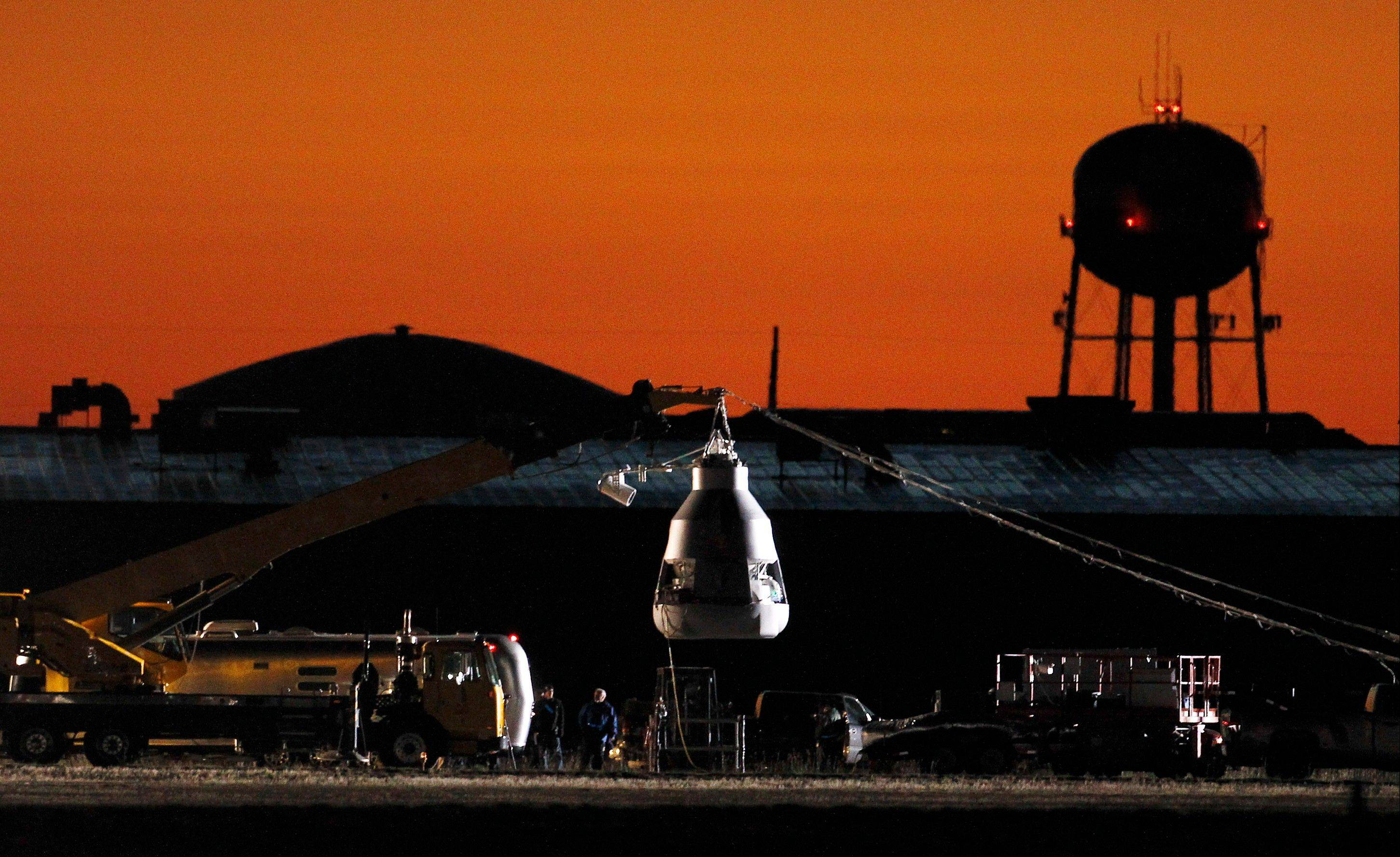 As the sun rises, workers prepare at the launch site, ahead of an attempt by Felix Baumgartner to break the speed of sound with his own body by jumping from a space capsule lifted by a helium balloon, Sunday, Oct. 14, 2012, in Roswell, N.M. Baumgartner plans to jump from an altitude of 120,000 feet, an altitude chosen to enable him to achieve Mach 1 in free fall, which would deliver scientific data to the aerospace community about human survival from high altitudes.