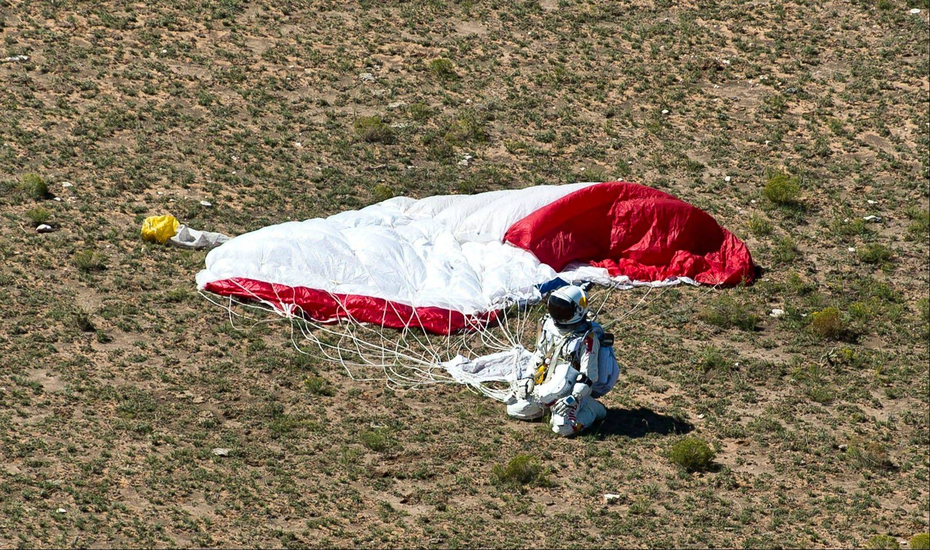 In this photo provided by Red Bull Stratos, pilot Felix Baumgartner of Austria lands in the desert after his successful jump on Sunday, Oct. 14, 2012 in Roswell, N.M. Baumgartner came down safely in the eastern New Mexico desert minutes about nine minutes after jumping from his capsule 128,097 feet, or roughly 24 miles, above Earth.