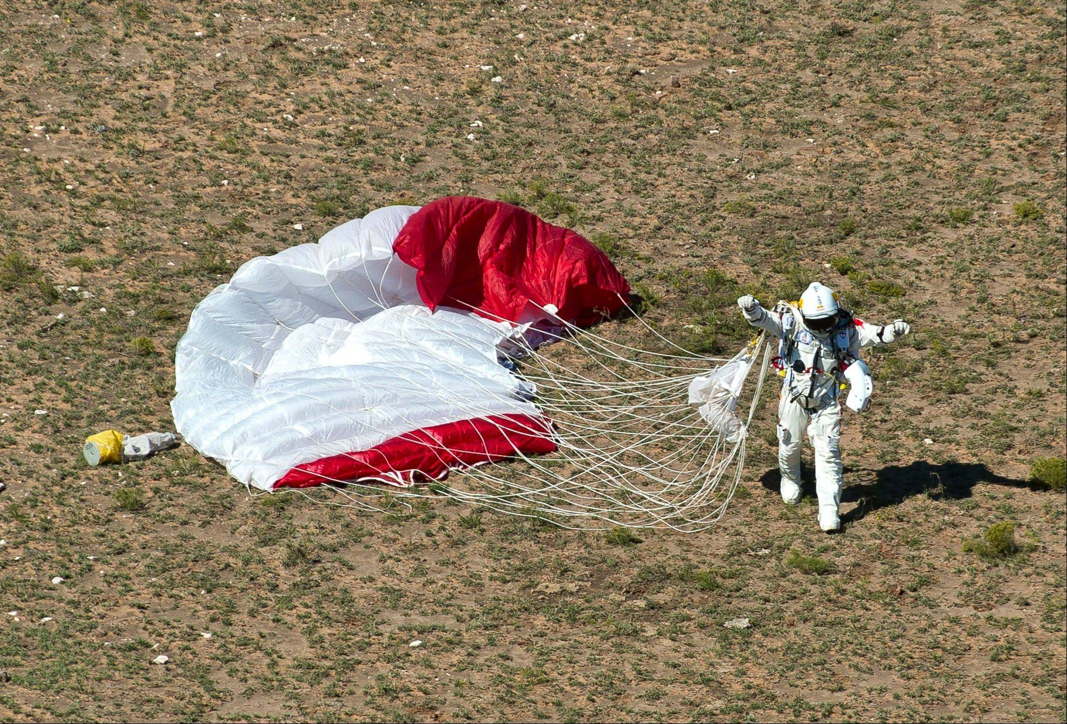 In this photo provided by Red Bull, pilot Felix Baumgartner of Austria celebrates after his successful jump on Sunday, Oct. 14, 2012 in Roswell, N.M. Baumgartner came down safely in the eastern New Mexico desert minutes about nine minutes after jumping from his capsule 128,097 feet, or roughly 24 miles, above Earth.