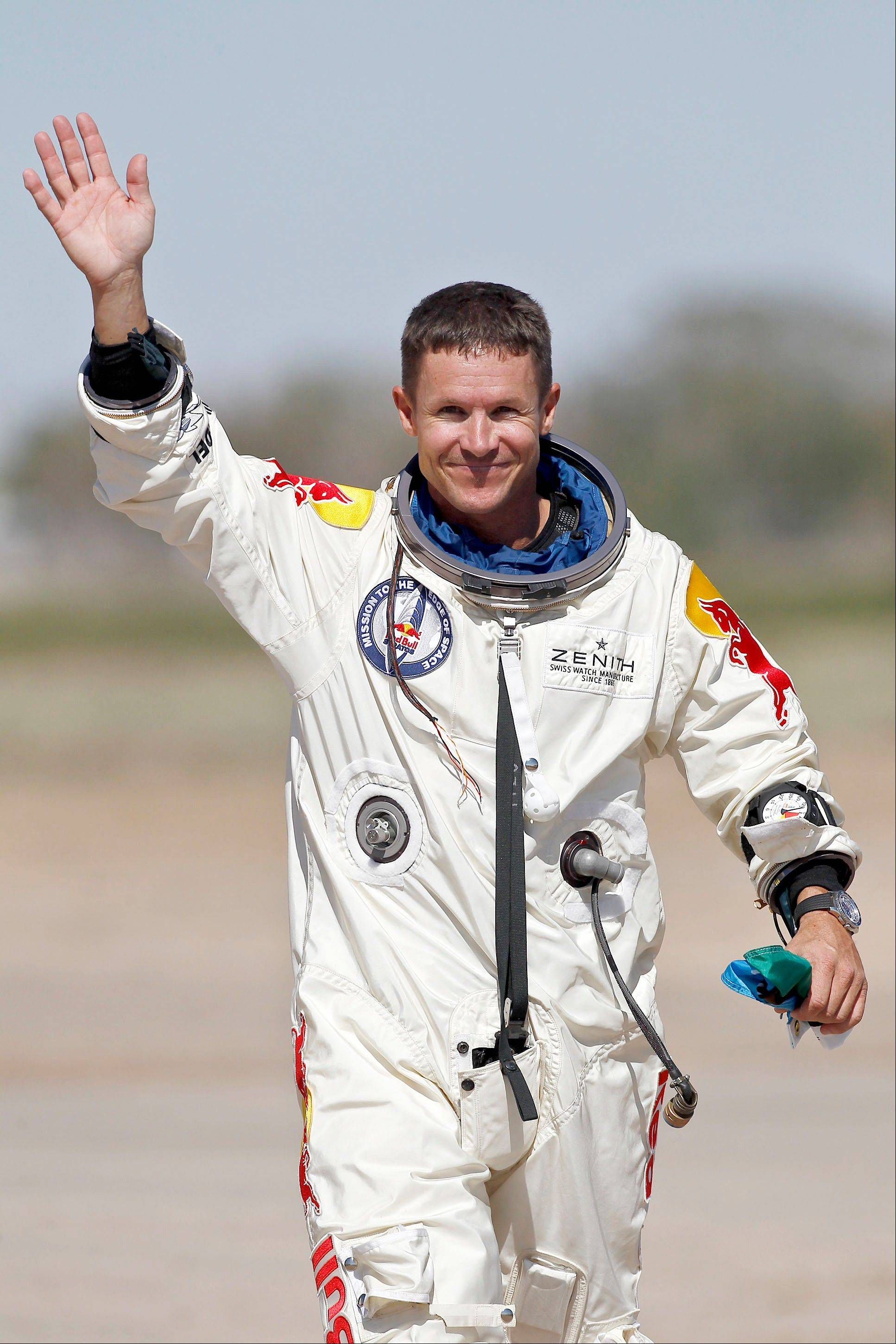 Felix Baumgartner, of Austria, waves to the crowd after successfully jumping from a space capsule lifted by a helium balloon at a height of just over 128,000 feet above the Earth's surface, Sunday, Oct. 14, 2012, in Roswell, N.M.