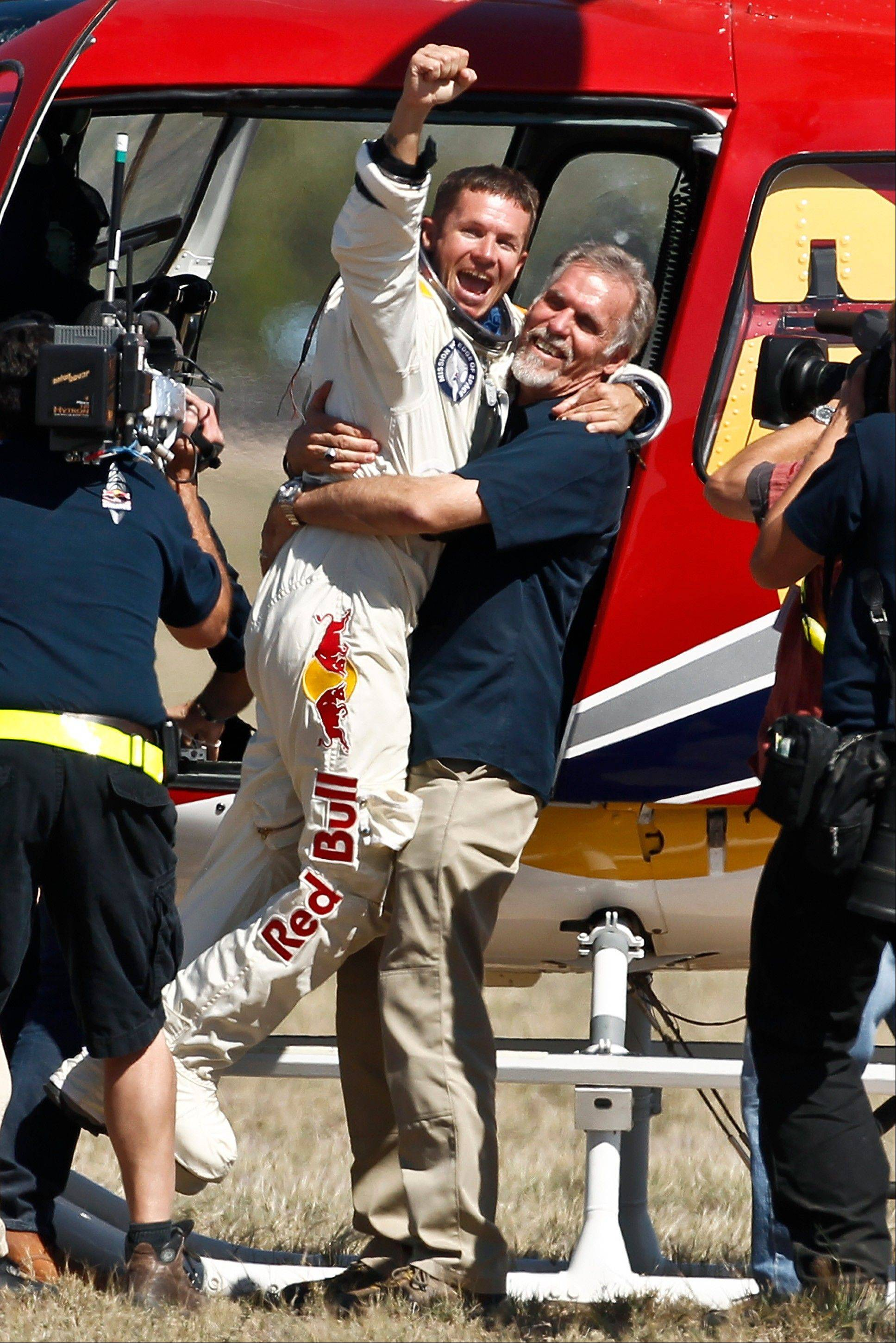 Felix Baumgartner, left, of Austria, celebrates with Art Thompson, Technical Project Director, after successfully jumping from a space capsule lifted by a helium balloon at a height of just over 128,000 feet above the Earth's surface, Sunday, Oct. 14, 2012, in Roswell, N.M. Baumgartner landed in the eastern New Mexico desert minutes after jumping from his capsule 28,000 feet (8,534 meters), or 24 miles (38.6-kilometer), above Earth.