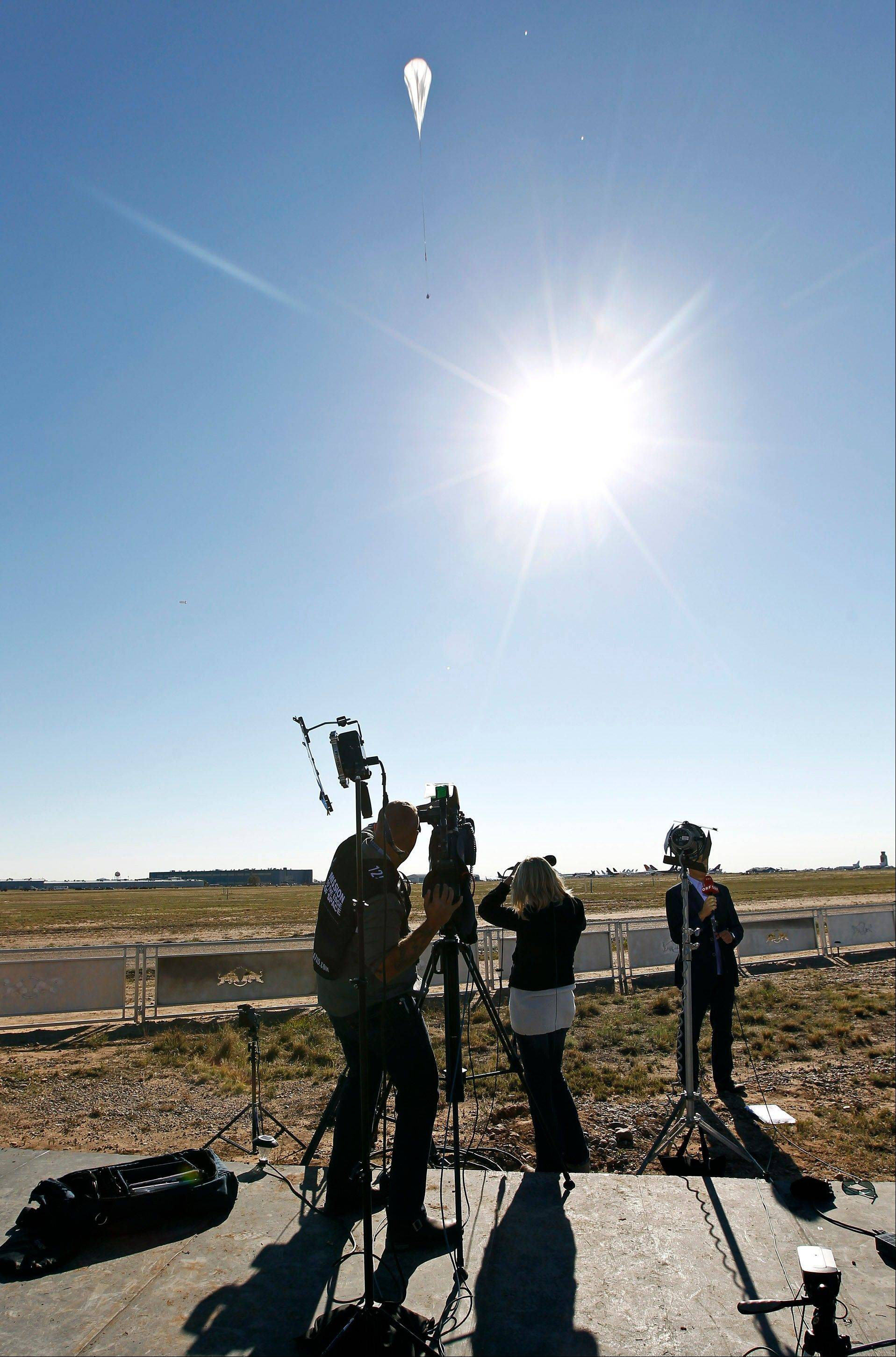 A television crew films the capsule and attached helium balloon, at top of frame, carrying Felix Baumgartner lifting off as he attempts to break the speed of sound with his own body by jumping from a space capsule lifted by a helium balloon, Sunday, Oct. 14, 2012, in Roswell, N.M. Baumgartner plans to jump from an altitude of 120,000 feet, an altitude chosen to enable him to achieve Mach 1 in free fall, which would deliver scientific data to the aerospace community about human survival from high altitudes.