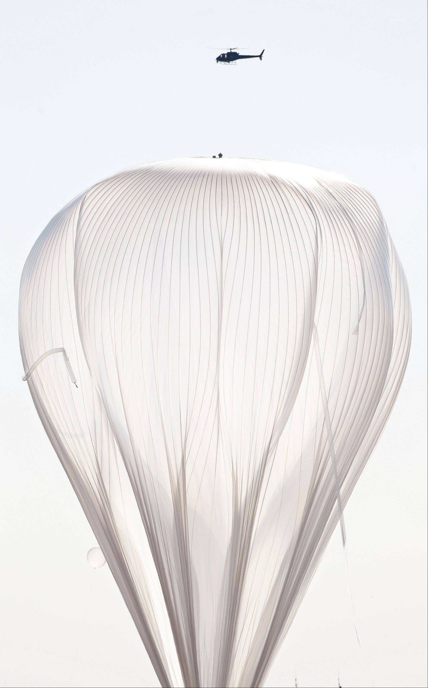 A helicopter hovers above the helium balloon, attached to the capsule carrying Felix Baumgartner, before he attempts to break the speed of sound with his own body by jumping from the space capsule, Sunday, Oct. 14, 2012, in Roswell, N.M. Baumgartner plans to jump from an altitude of 120,000 feet, an altitude chosen to enable him to achieve Mach 1 in free fall, which would deliver scientific data to the aerospace community about human survival from high altitudes.