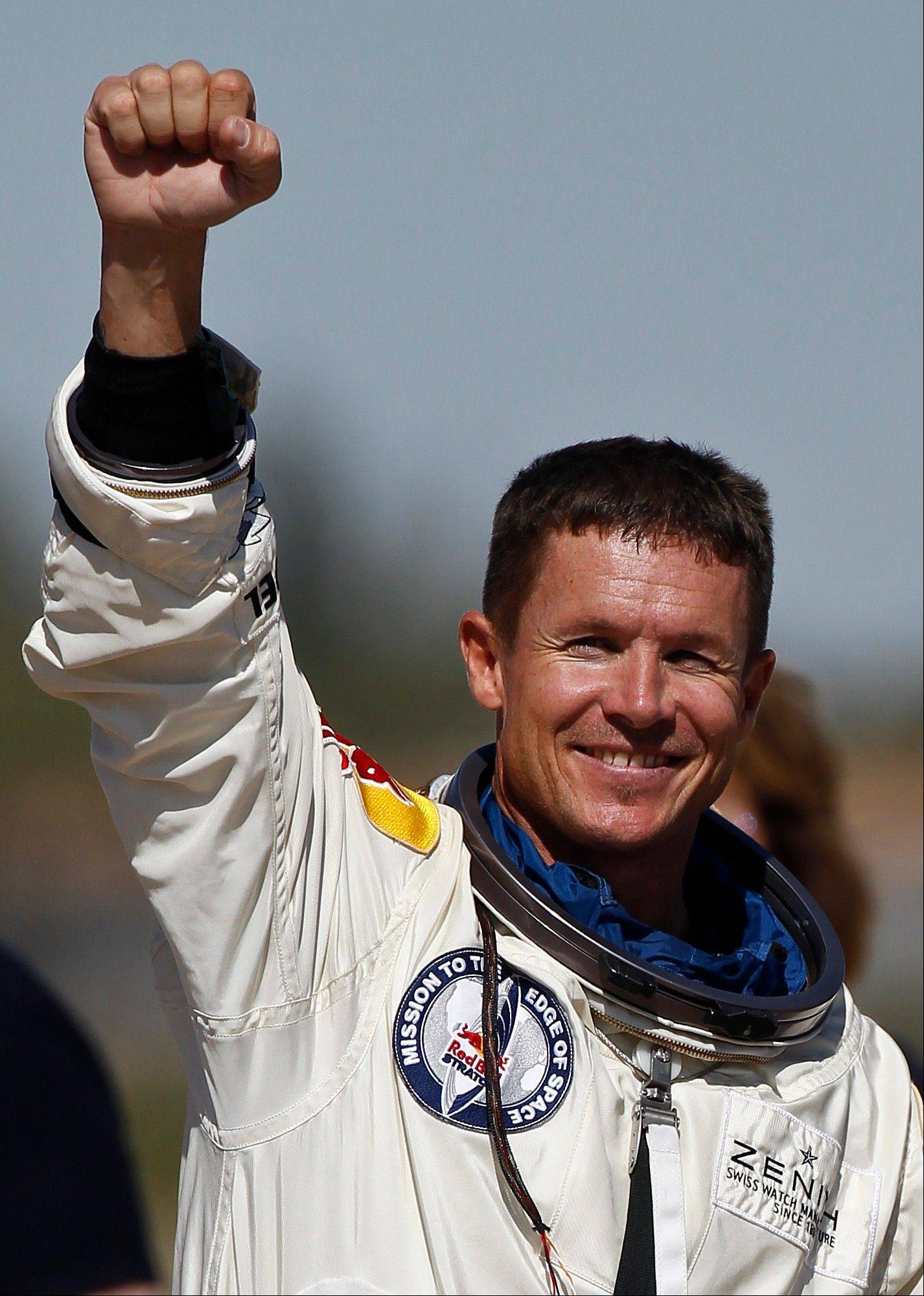 Felix Baumgartner, of Austria, pumps his fist to the crowd after successfully jumping from a space capsule lifted by a helium balloon at a height of just over 128,000 feet above the Earth's surface Sunday in Roswell, N.M. Baumgartner came down safely in the eastern New Mexico desert minutes about nine minutes after jumping from his capsule 128,097 feet, or roughly 24 miles, above Earth.
