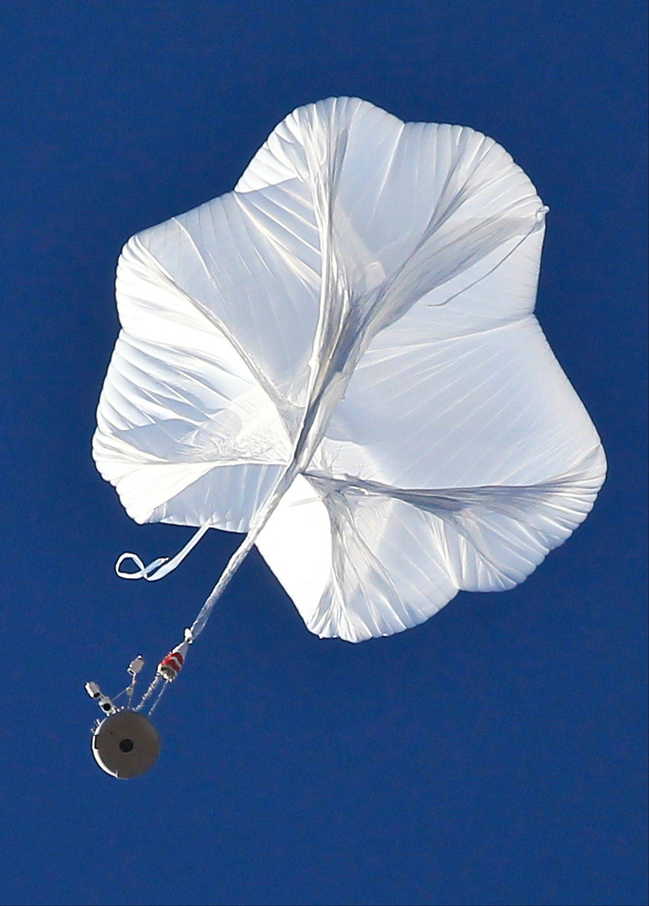 The capsule, bottom left, and attached helium balloon carrying Felix Baumgartner lifts off as he attempts to break the speed of sound with his own body by jumping from a space capsule lifted by a helium balloon Sunday in Roswell, N.M.