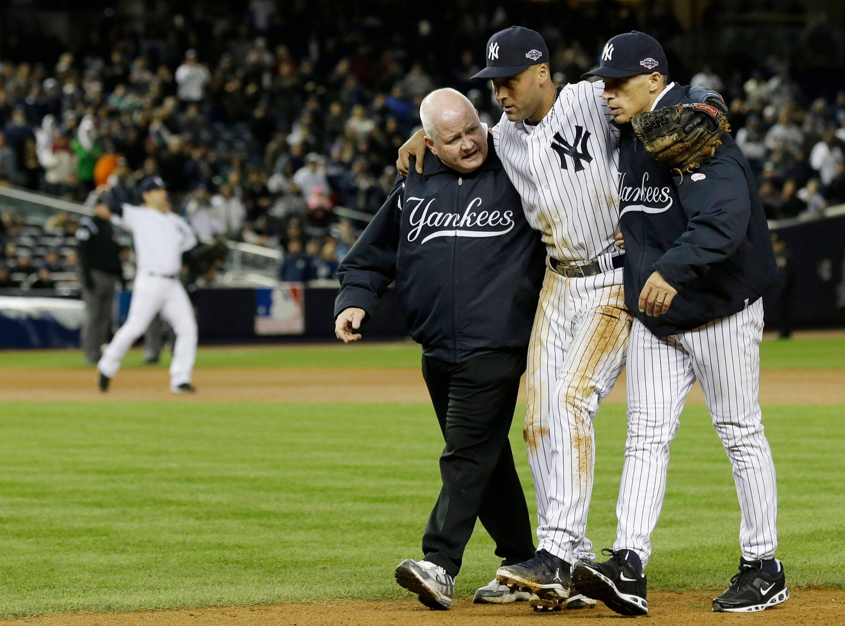 Trainer Steve Donohue, left, and Yankees manager Joe Girardi help Derek Jeter off the field after he suffered a broken ankle late in Saturday's Game 1 of the ALCS.