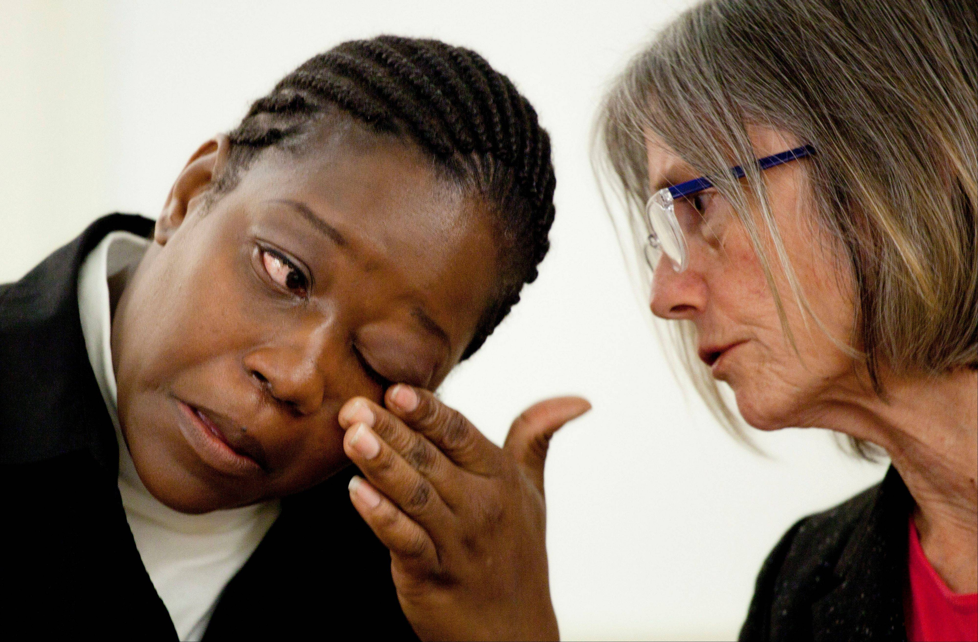 Rubbie McCoy, left, a plaintiff in a lawsuit filed against Morgan Stanley, reacts while describing her housing situation during a news conference Monday in New York. With her is attorney Elizabeth Cabraser. McCoy and four other Detroit homeowners have filed a lawsuit claiming Morgan Stanley discriminated against black homeowners and violated federal civil rights laws.