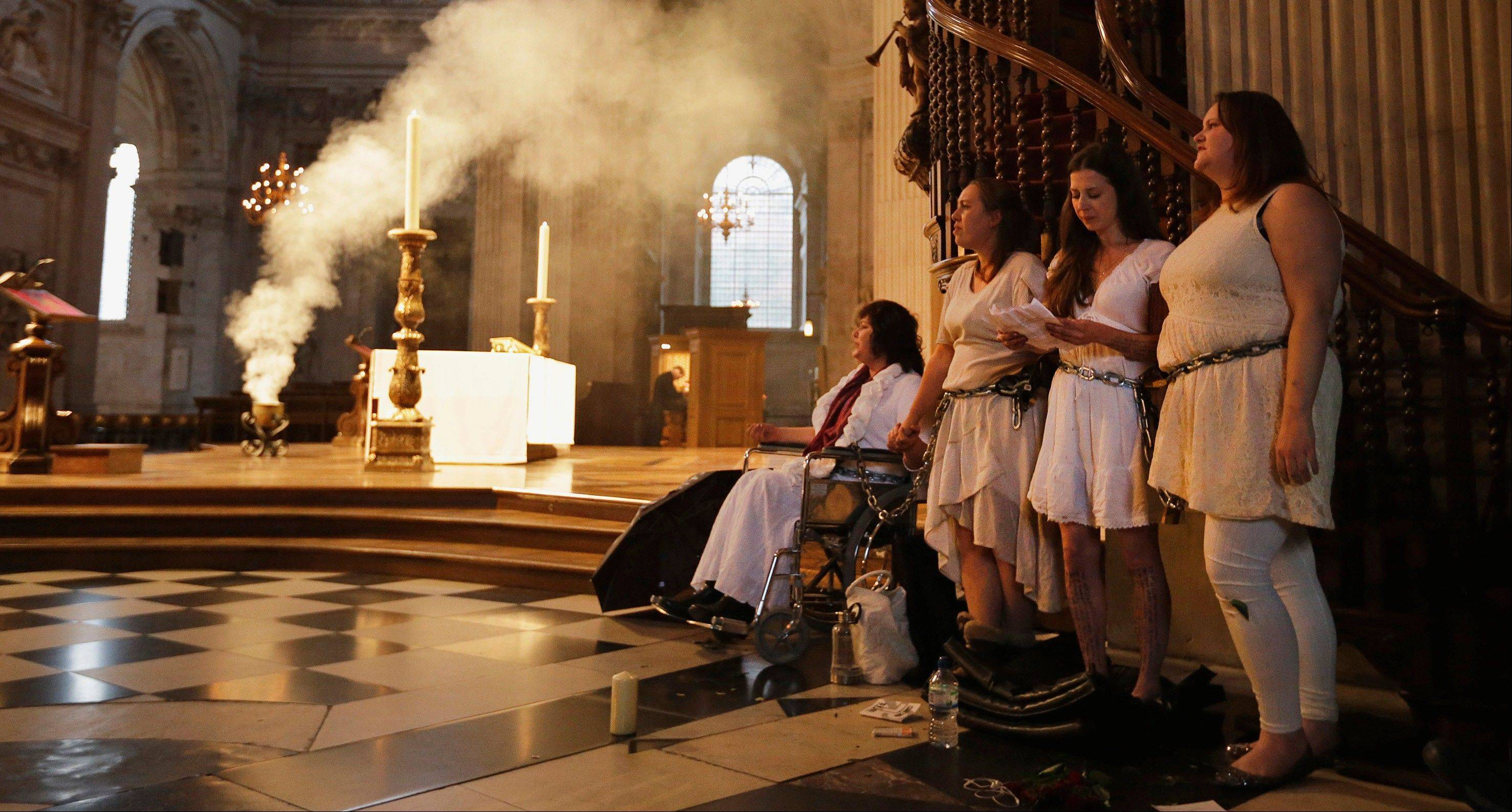 Four women activists of the Occupy movement protest chained to the pulpit inside St Paul's Cathedral as preparations for evensong take place in London, Sunday.