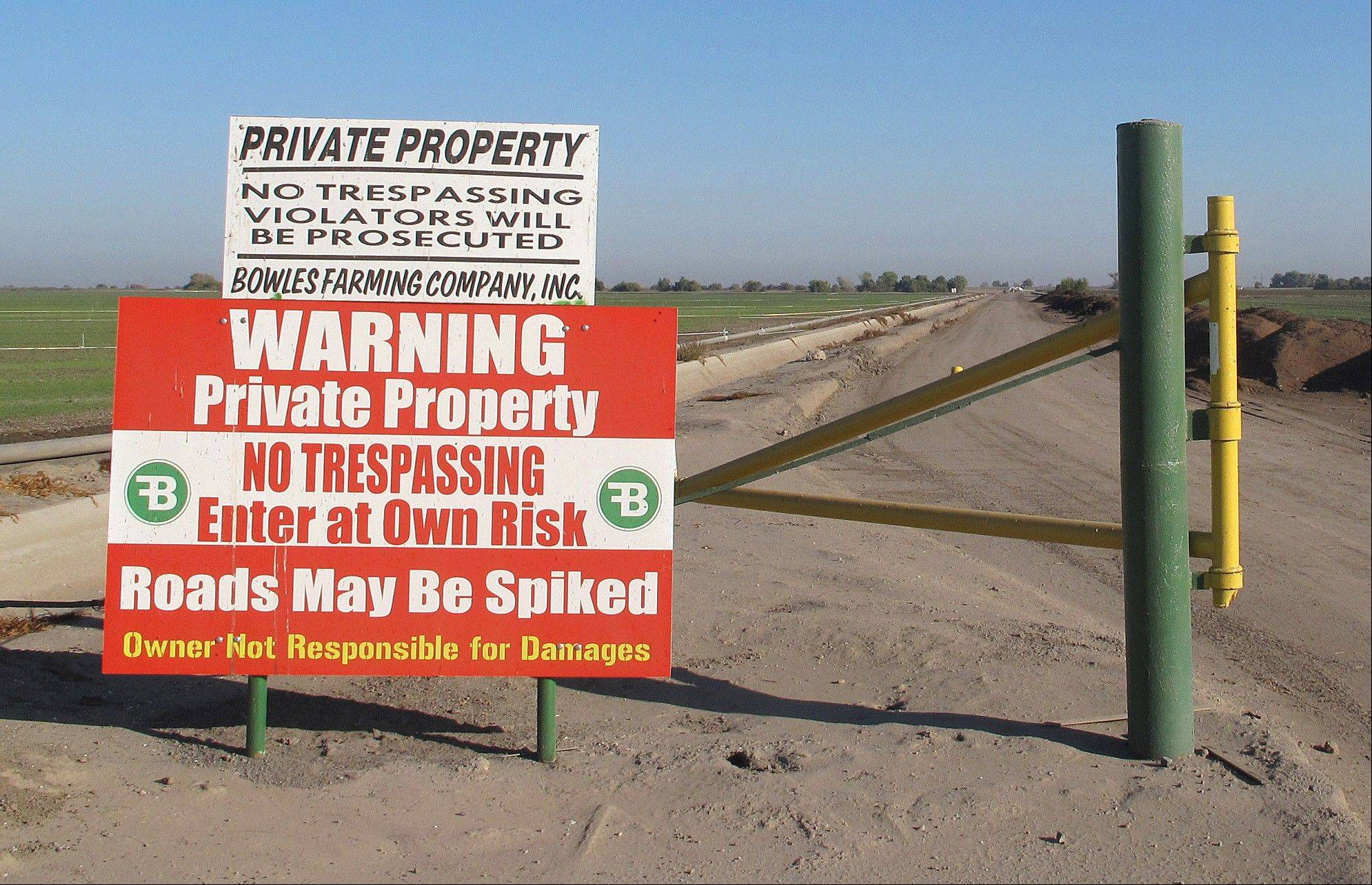 Warning signs farmer Cannon Michael put up after burying spike strips on his property to flatten the tires of metal thieves in Dos Palos, Calif.