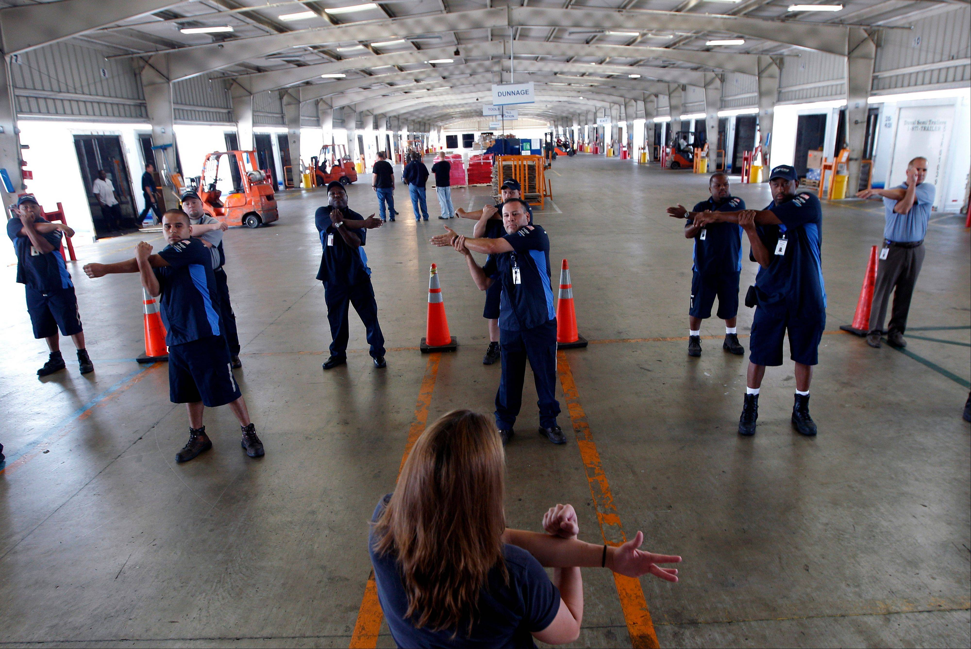Wellness coach Kara Whitcomb leads truckers in a stretching regime before their driving shifts start at Con-way Freight in Garland, Texas.