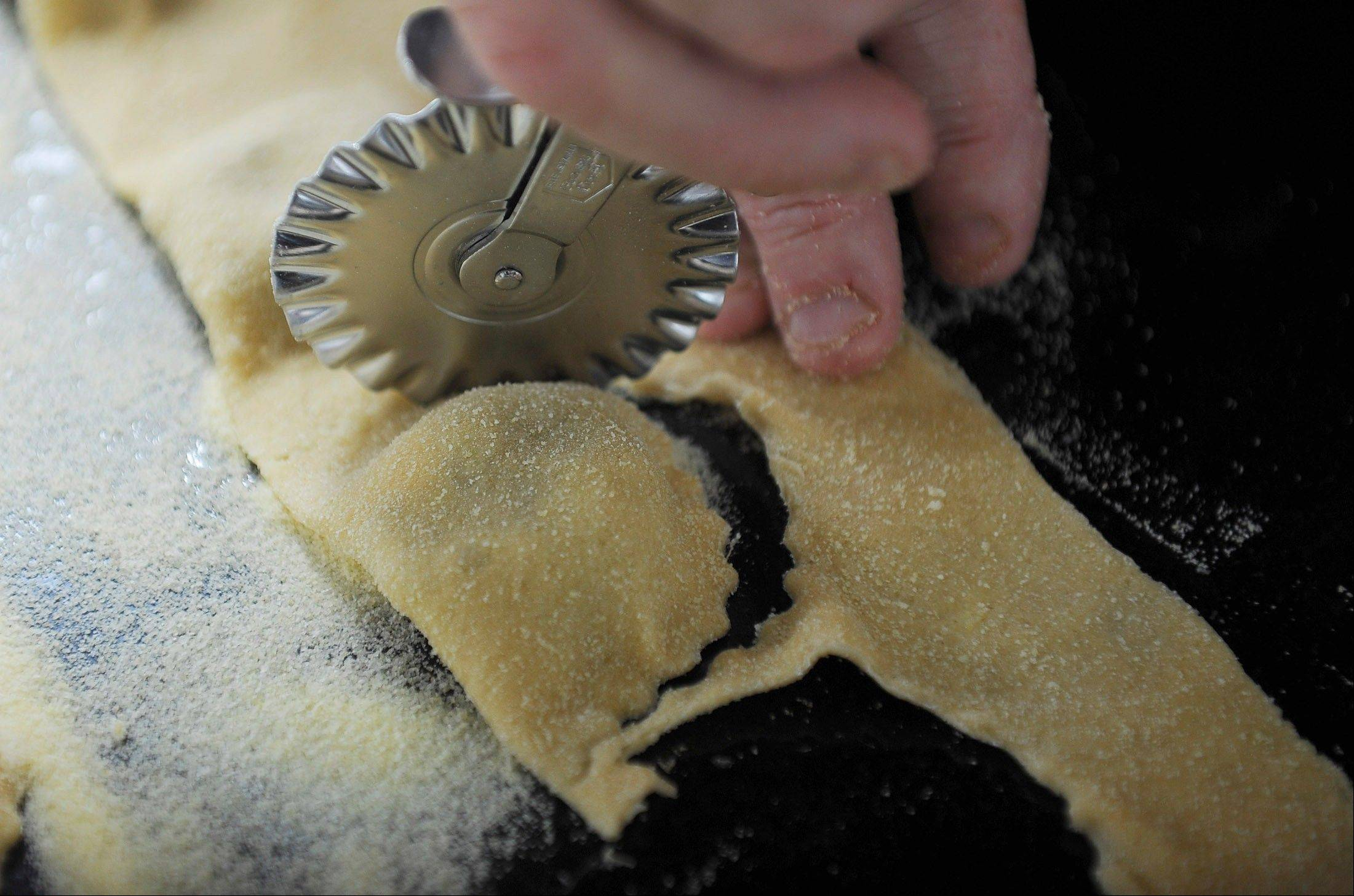 A pasta cutter is used to form Roasted Brussels Sprout Agnolotti.