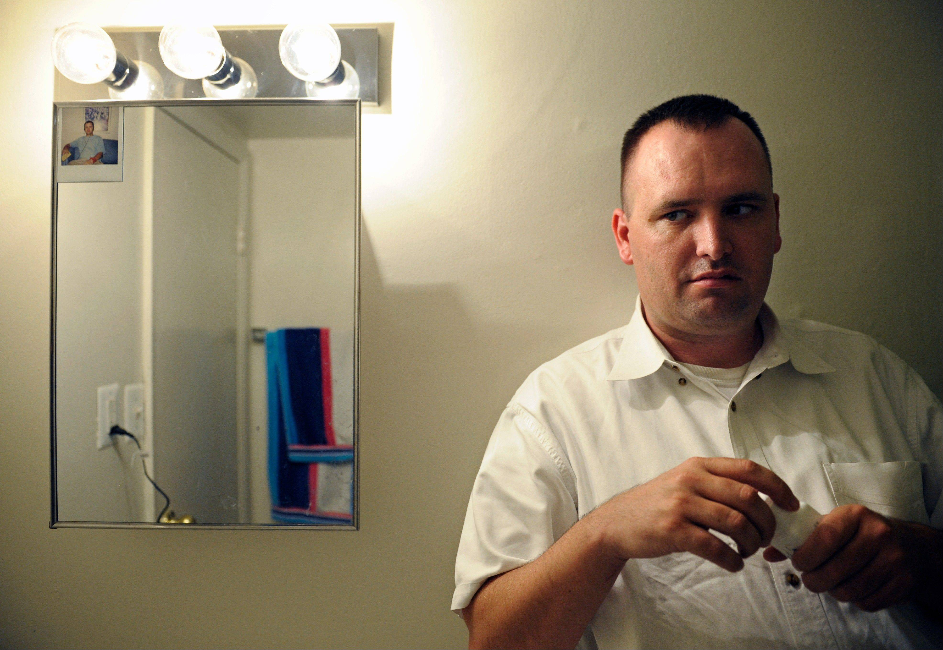 "Kevin Earley, 33, holds a bottle of his antipsychotic medication as he stands next to the medicine cabinet, which has an old photo taped to it, in the bathroom of his apartment that he shares with a roommate. Of the photo, Earley says, ""It reminds me to take my medicine every day and reminds me of where I have been and what I have been through."""