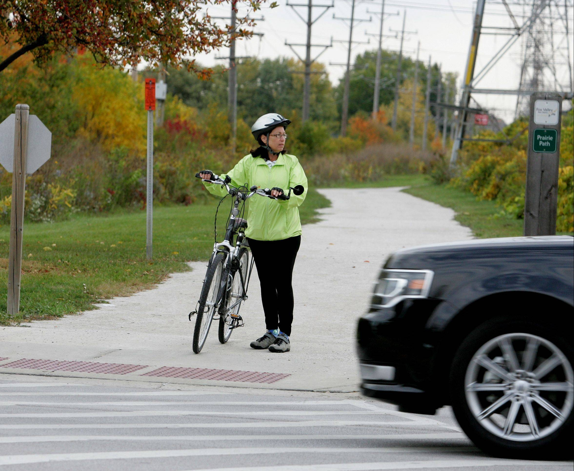 Lynn Mitchell of Sugar Grove waits to cross Farnsworth Avenue in Aurora on the Illinois Prairie Path. Two lighted signs will be installed at the crossing after Mitchell pushed for safety improvements.