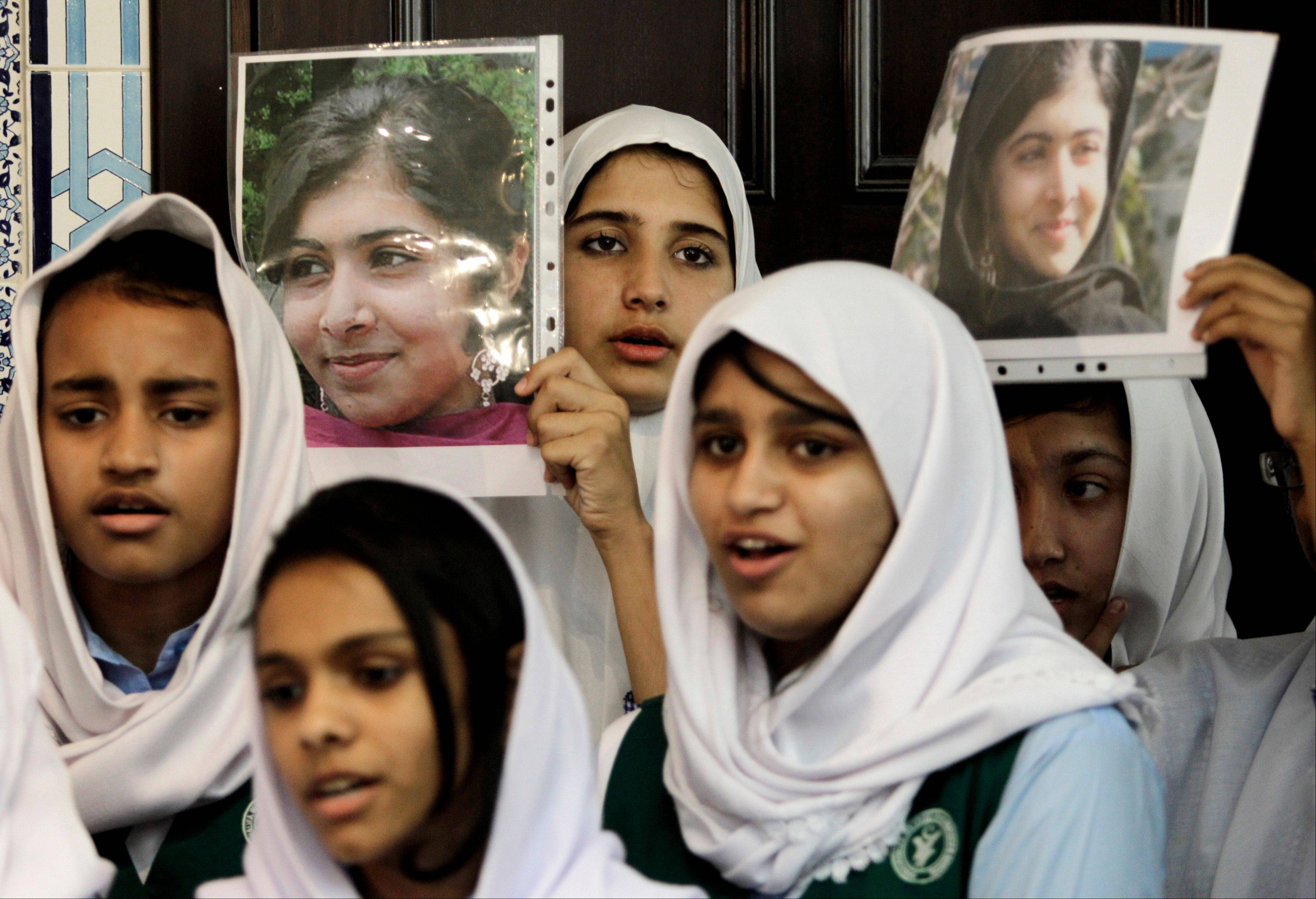 Pakistani students sing as they hold pictures of 14-year-old schoolgirl Malala Yousufzai, who was shot last Tuesday by the Taliban for speaking out in support of education for women, during a tribute at the Pakistani Embassy in Abu Dhabi, United Arab Emirates, Monday.
