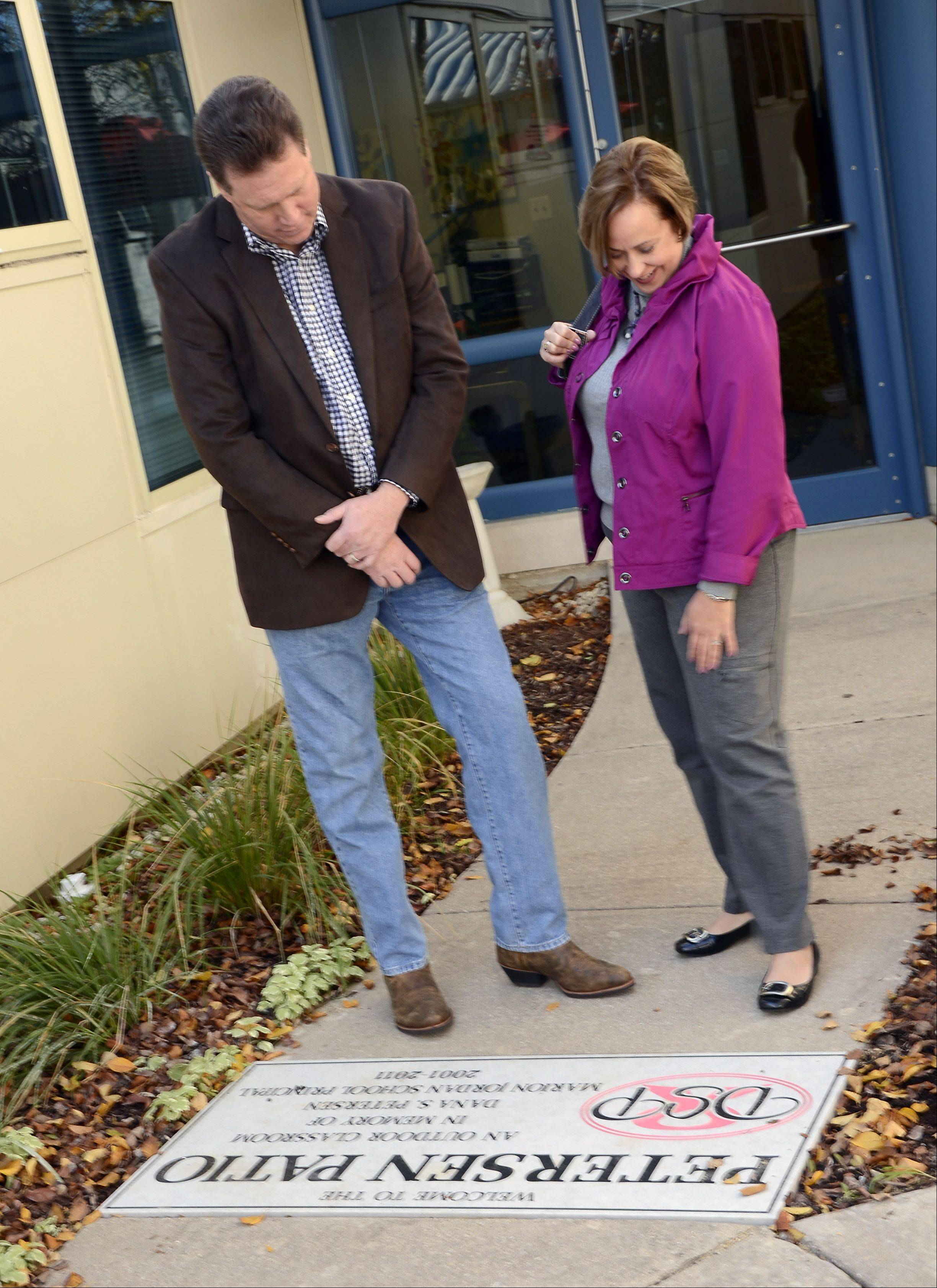 Dave Starr and his wife Karen Starr, of Wildwood, Mo., look at the plaque dedicated to his sister Dana Petersen's memory Monday at Marion Jordan School in Palatine. Petersen was the school's principal from 2001 to 2011.