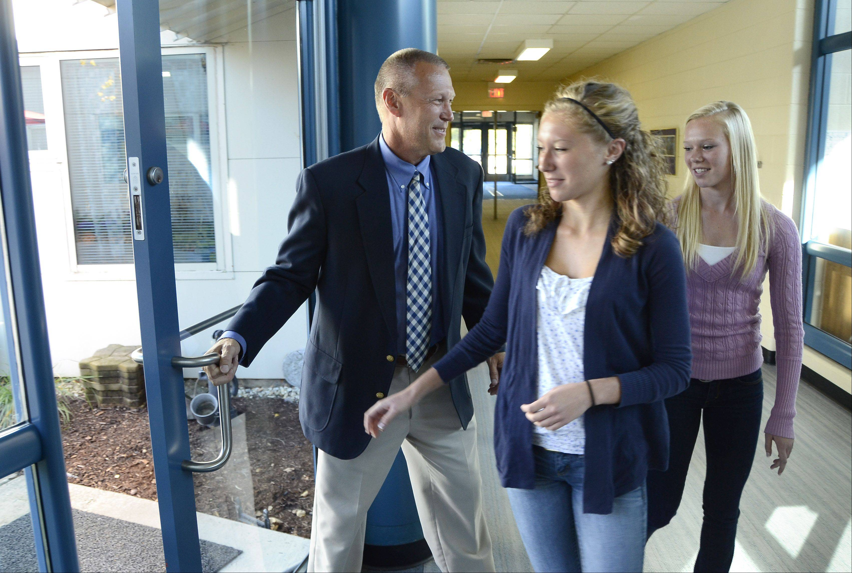 Tom Petersen and his daughters, from left, Emily Petersen and Carli Petersen, are the first to enter the Dana Petersen Patio after a dedication ceremony Monday at Marion Jordan School in Palatine. The courtyard is named after Tom's late wife Dana, who was principal at the school. It was a vision of hers to transform the space into an outdoor classroom.