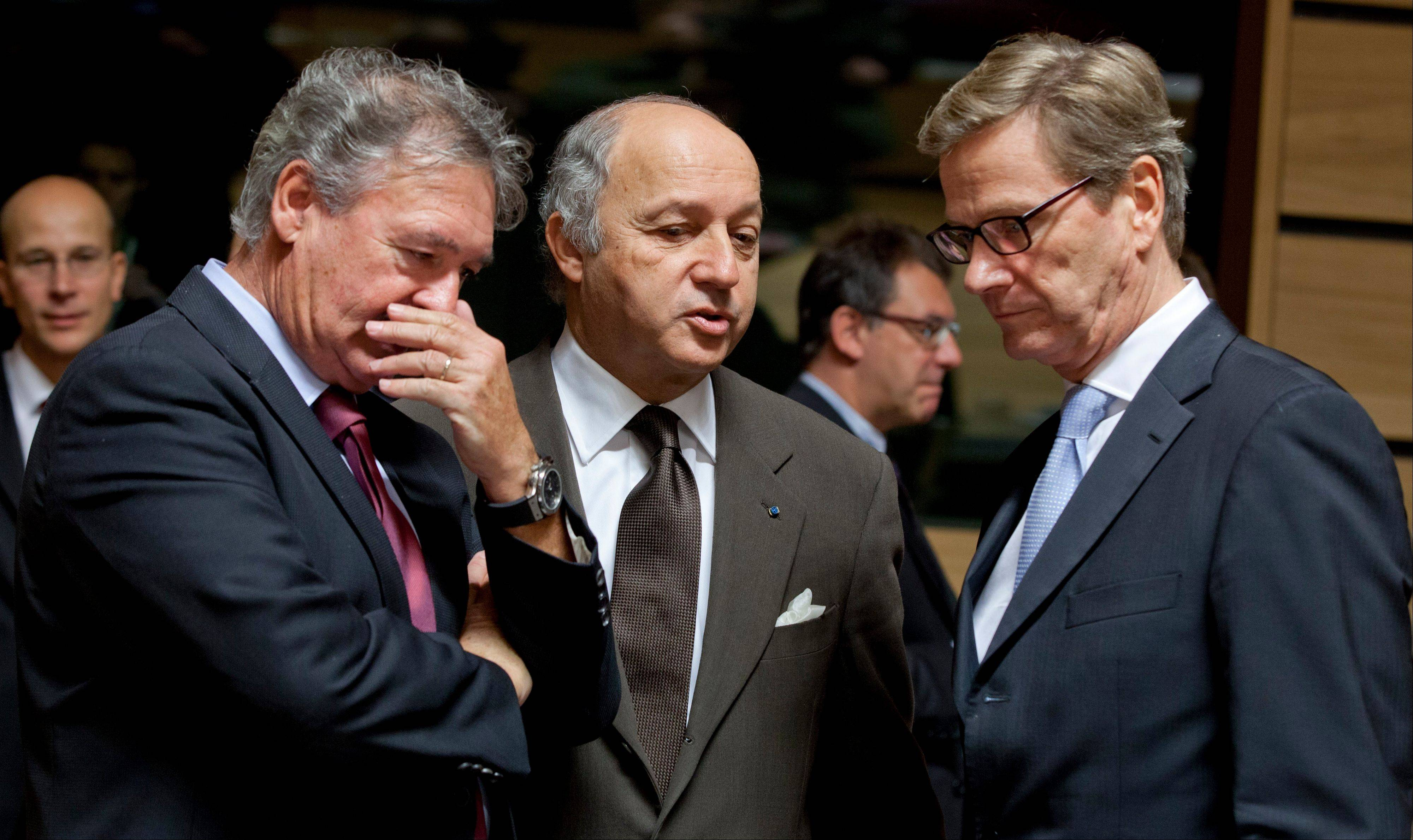 Luxembourg's Foreign Minister Jean Asselborn, left, French Foreign Minister Laurent Fabius and German Foreign Minister Guido Westerwelle share a word during a meeting of EU Foreign Ministers in Luxembourg on Monday. Britain, Germany and France say they expect the European Union to approve even tougher sanctions on Iran to prevent it from developing nuclear weapons.