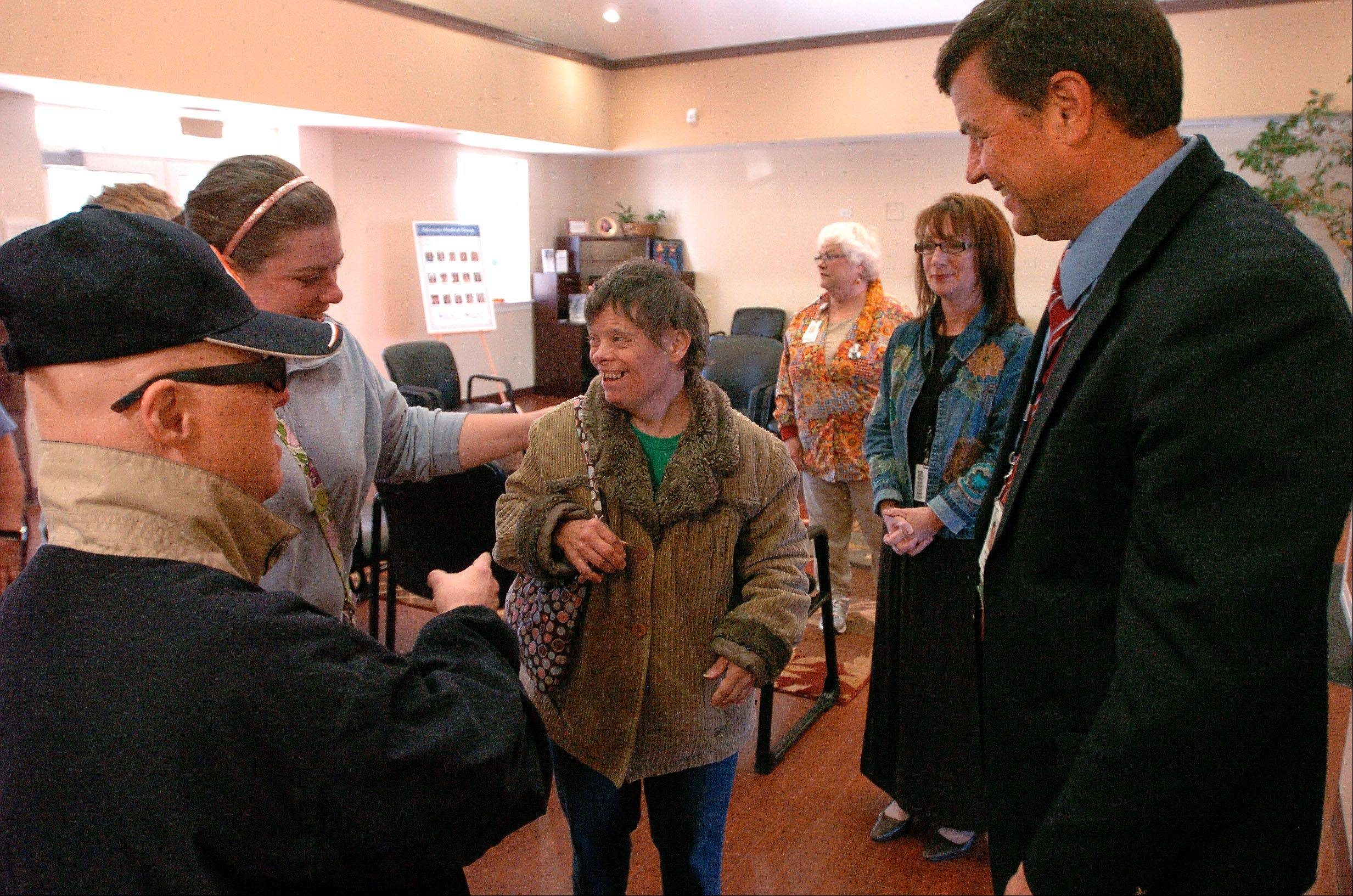Dr. Brian Chicoine, Medical Director of Advocate Lutheran General Hospitals Adult Down Syndrome Center, right, greets patients Paul Franklin, left, and Jill Sowins, center, during the open house.